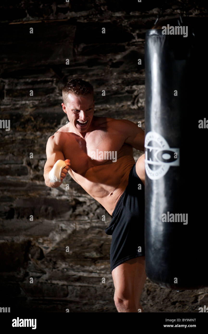 Un hombre kick boxing en el gimnasio. Imagen De Stock