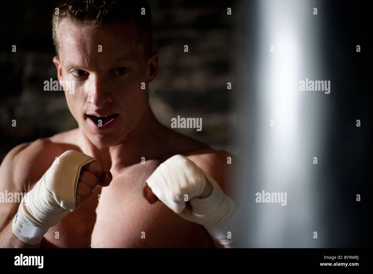 Un hombre físicamente apto ejercicios utilizando un saco de boxeo en un gimnasio. Imagen De Stock