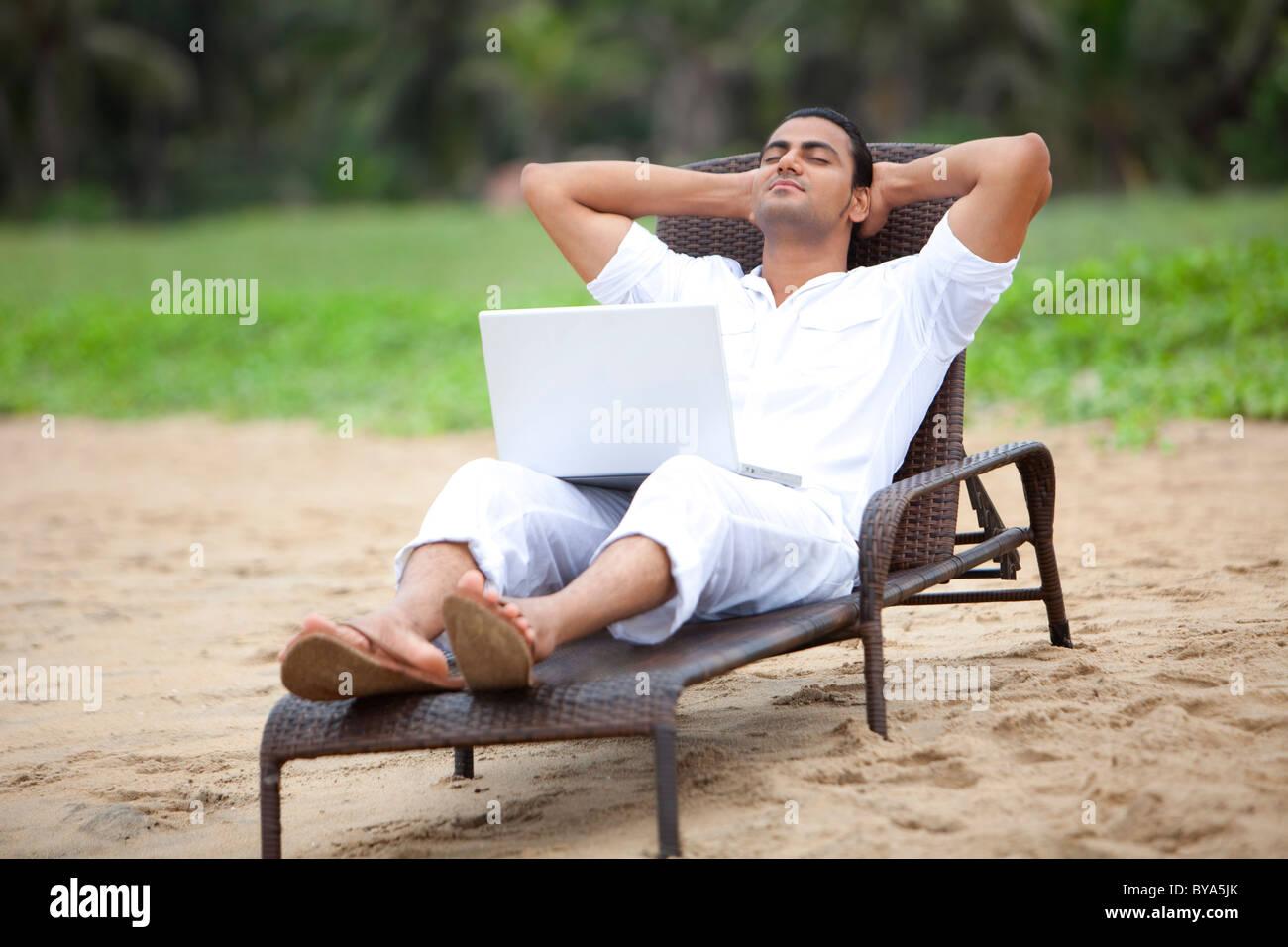 El hombre tomando una siesta en una playa Imagen De Stock