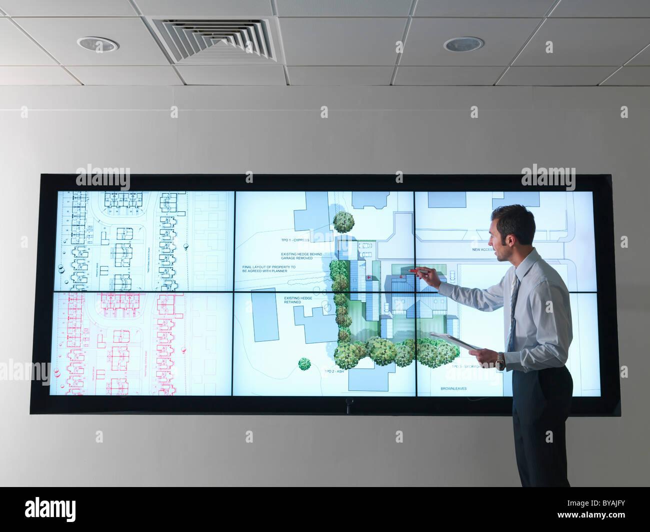 El arquitecto trabaja en planes en la pantalla Foto de stock