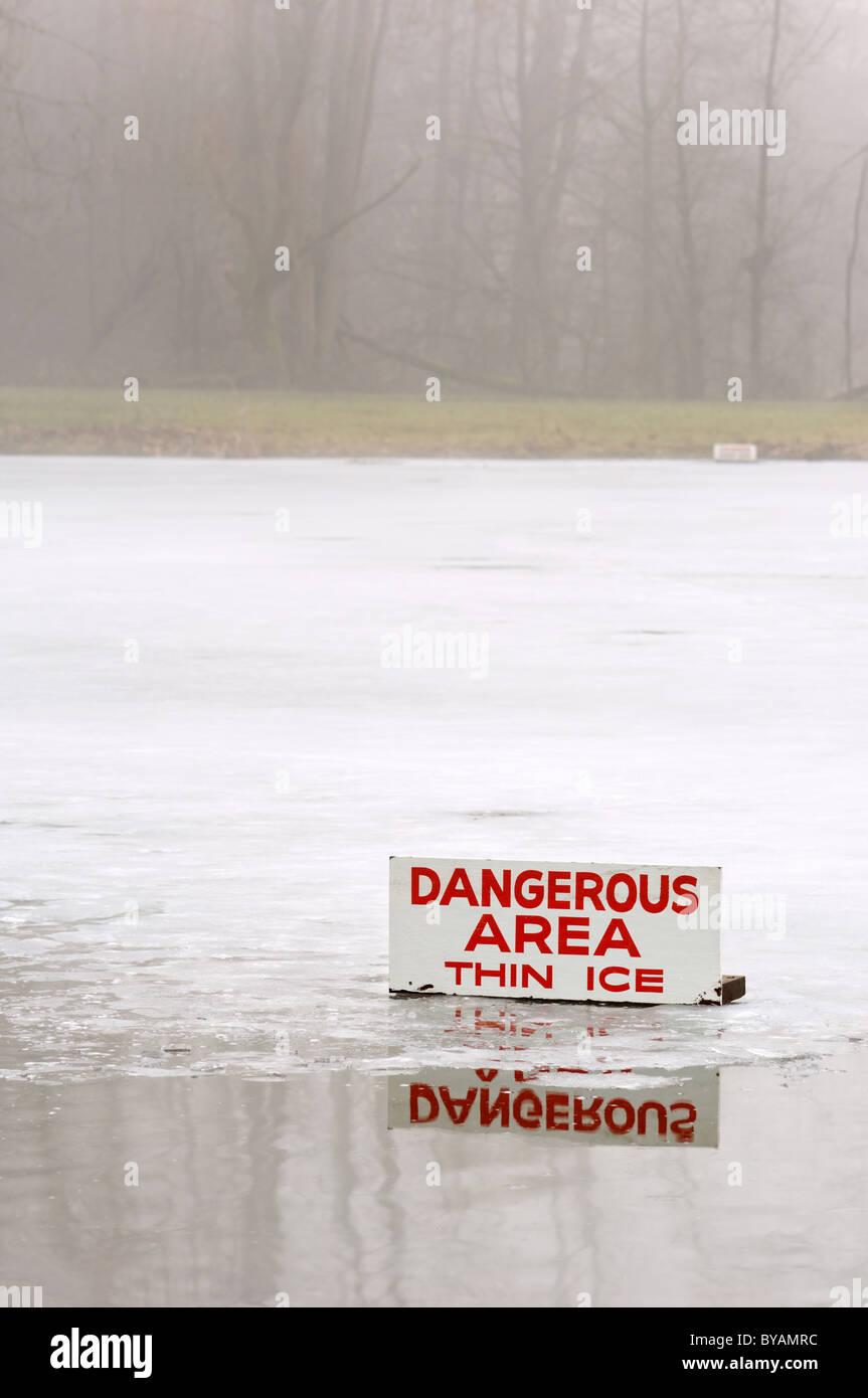 Un estanque cubierto con una fina capa de hielo con algunas aguas abiertas, y un cartel que indica el peligro durante Imagen De Stock