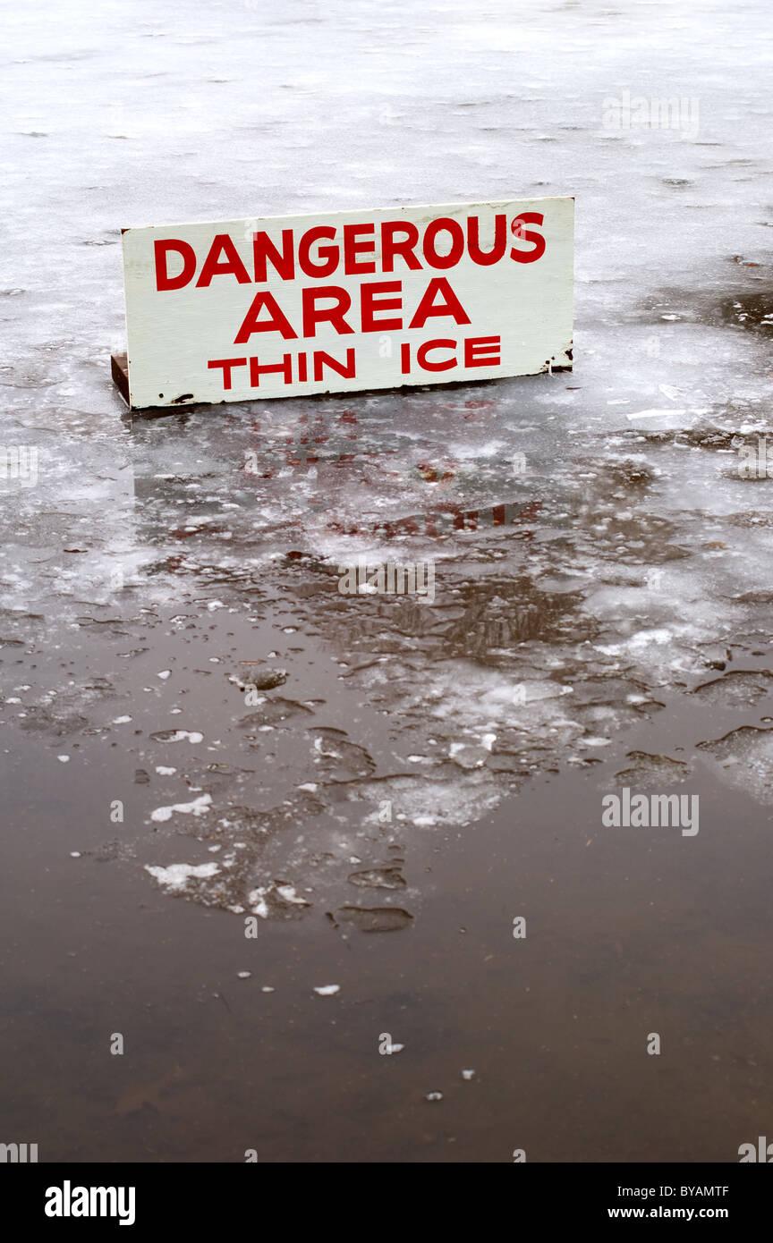 Un estanque cubierto con una fina capa de hielo con algunas aguas abiertas, y un cartel que indica el peligro. Imagen De Stock