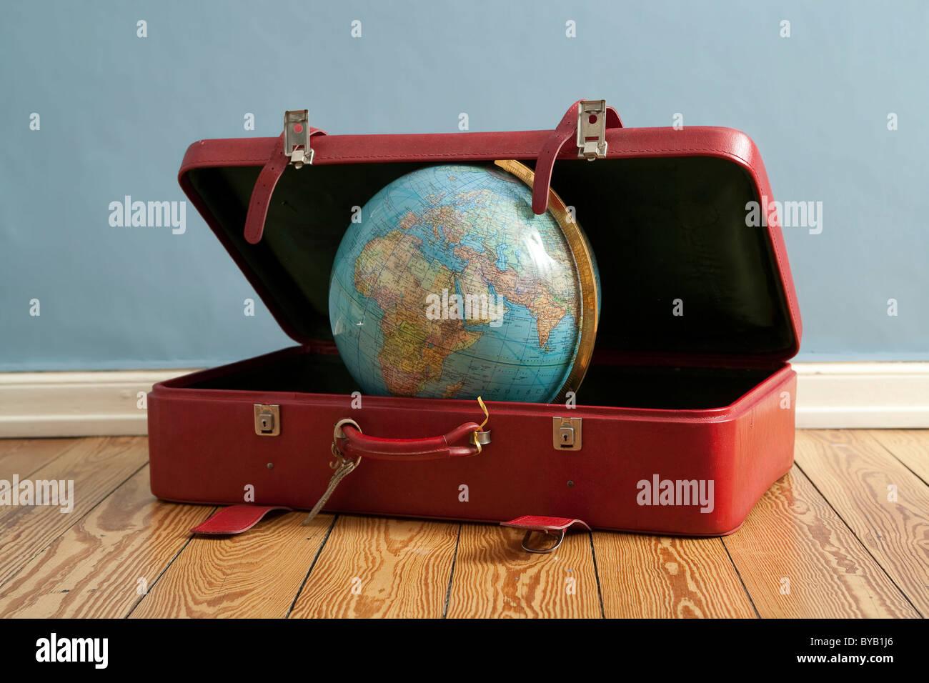 Mundo en una maleta, imagen simbólica para viajar, vacaciones, viaje alrededor del mundo Imagen De Stock