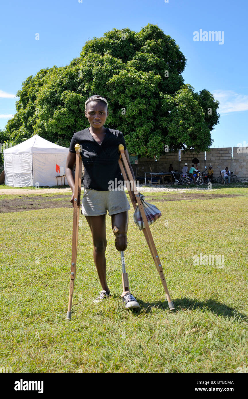 Mujer joven, víctima del terremoto de enero de 2010, con una pierna protésica y muletas que ella recibió Imagen De Stock