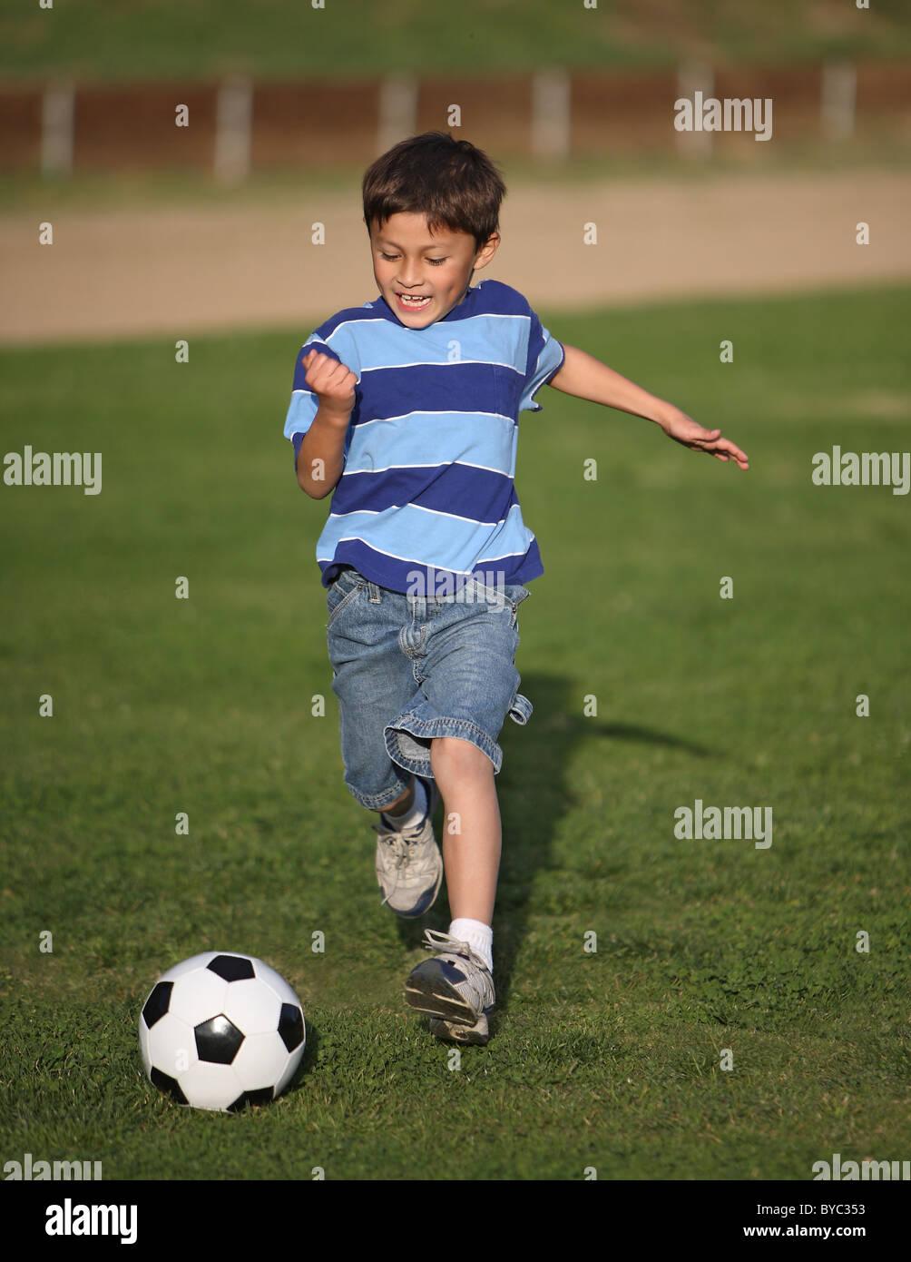 Auténtico chico Latino feliz jugando con una pelota de fútbol en el campo vistiendo camiseta a rayas azules. Imagen De Stock