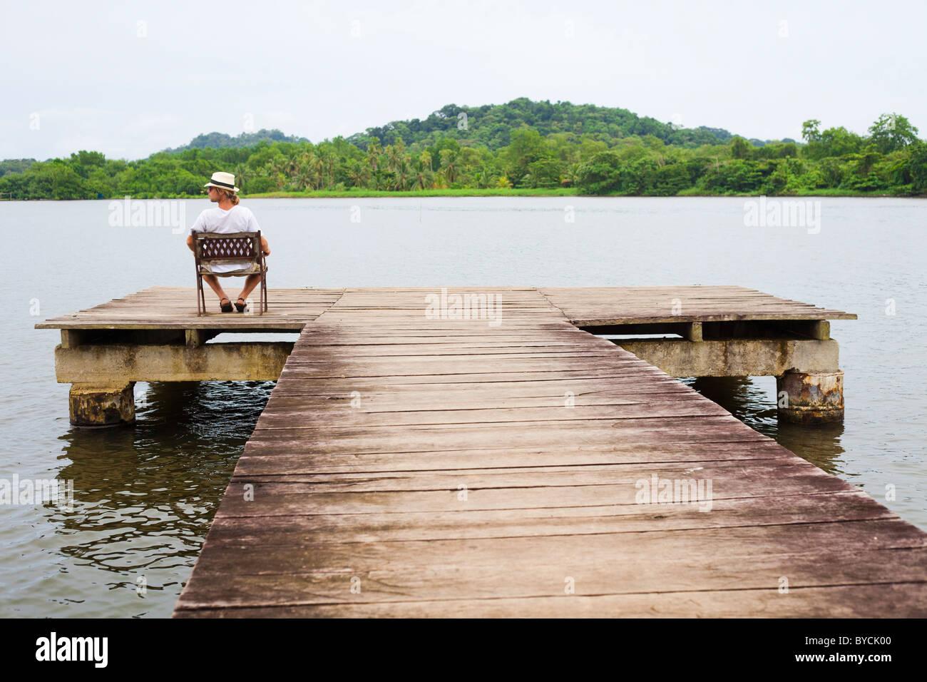 6b3201891bd80 Hombre de sombrero blanco sentado en una silla en el extremo de un muelle  en Panamá