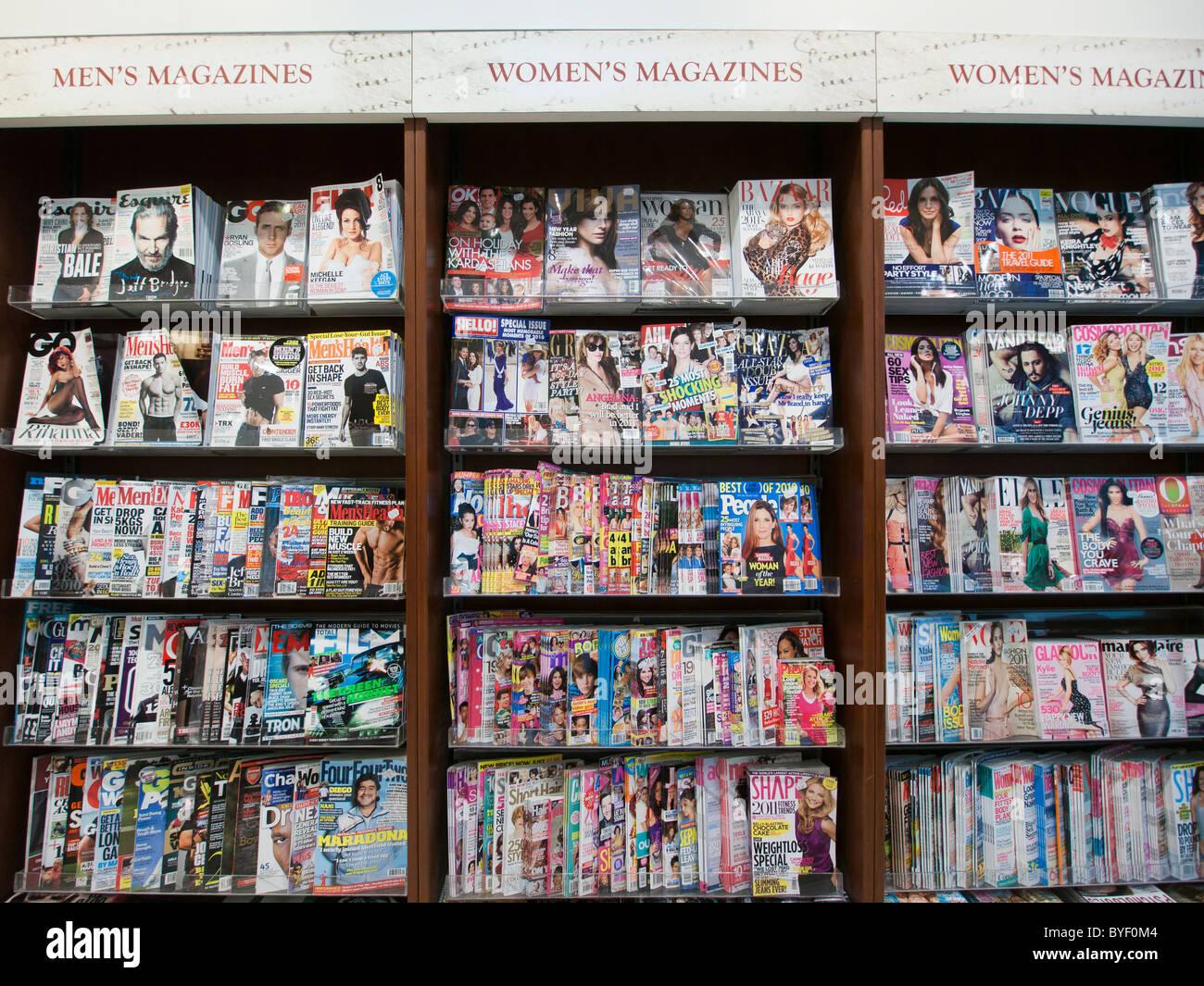 Los hombres y las revistas femeninas en exhibición en una tienda Imagen De Stock
