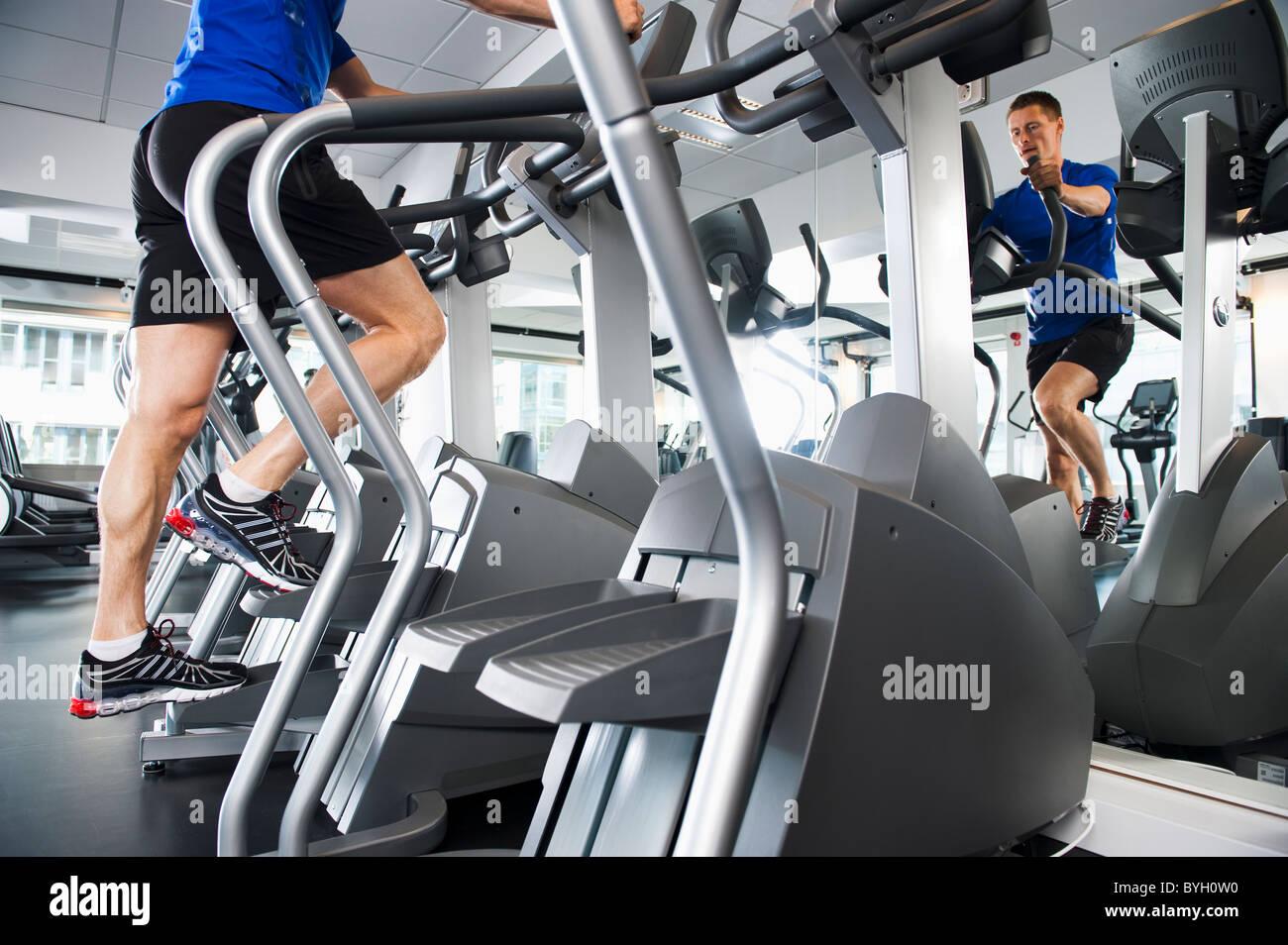 Hombre corriendo en máquinas de ejercicio en el gimnasio Imagen De Stock