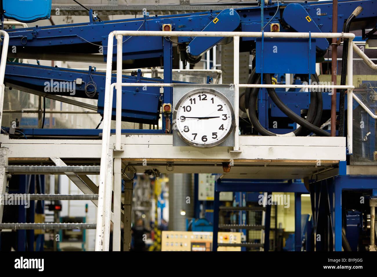 Escaleras de metal montada al lado del reloj en la fábrica de la loseta Imagen De Stock