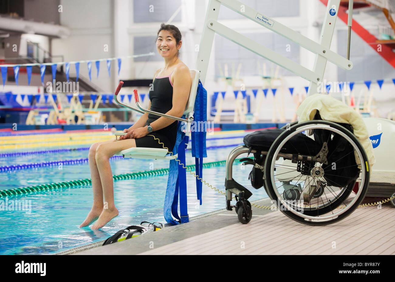Un parapléjico mujer entra en una piscina en un ascensor con su silla de ruedas en el borde de la piscina; Imagen De Stock