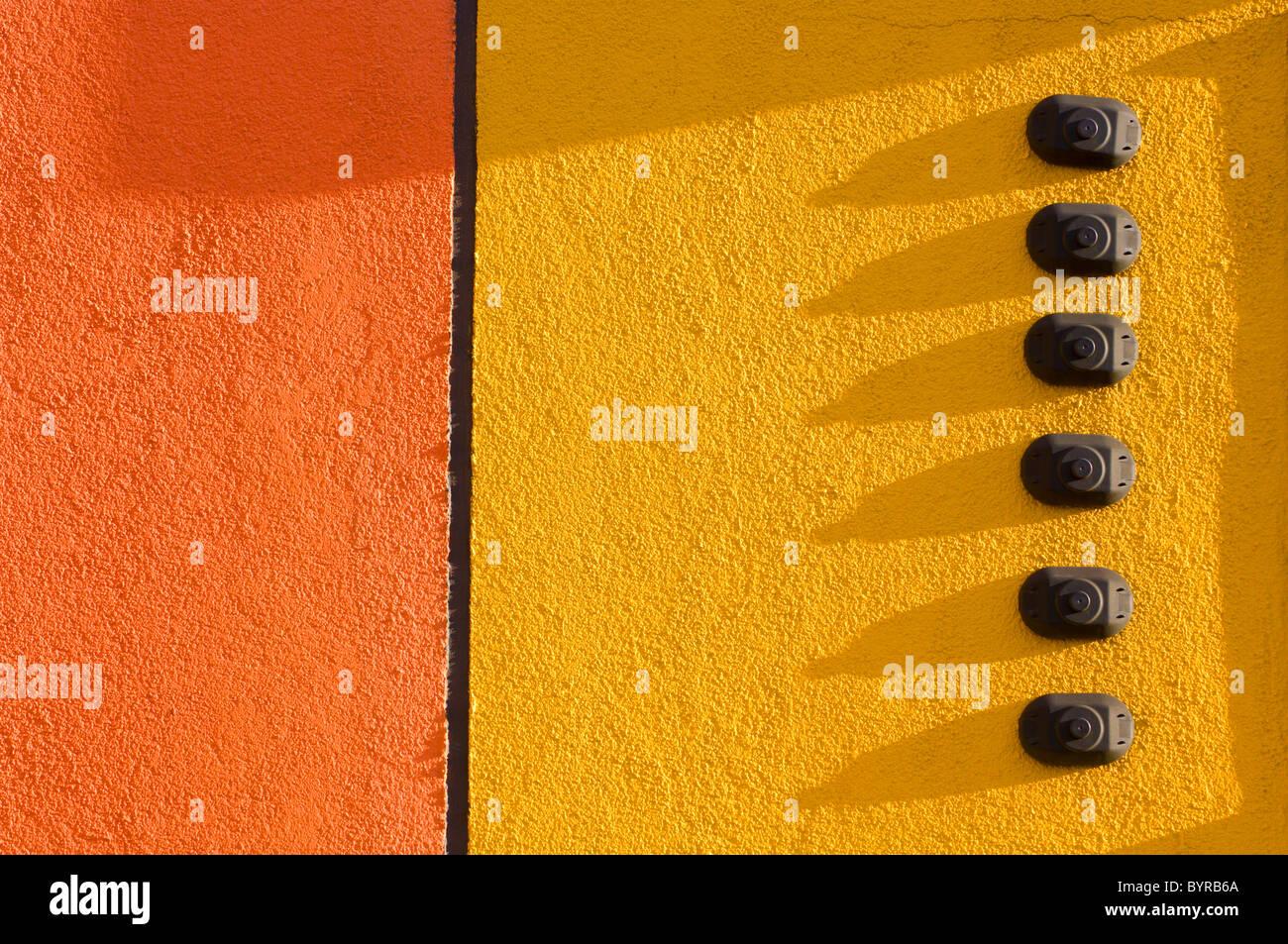 Pared de estuco naranja y amarilla con 6 timbres; st. Albert, Alberta, Canadá Imagen De Stock