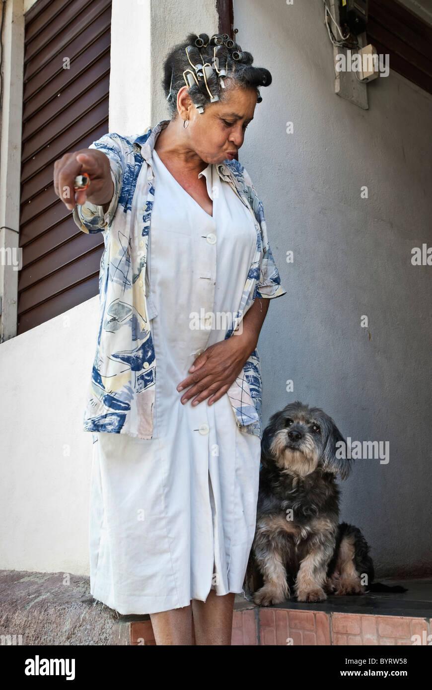 Mujer con rizadores de pelo y su perro, Santiago de Cuba, Cuba, el Caribe. Imagen De Stock