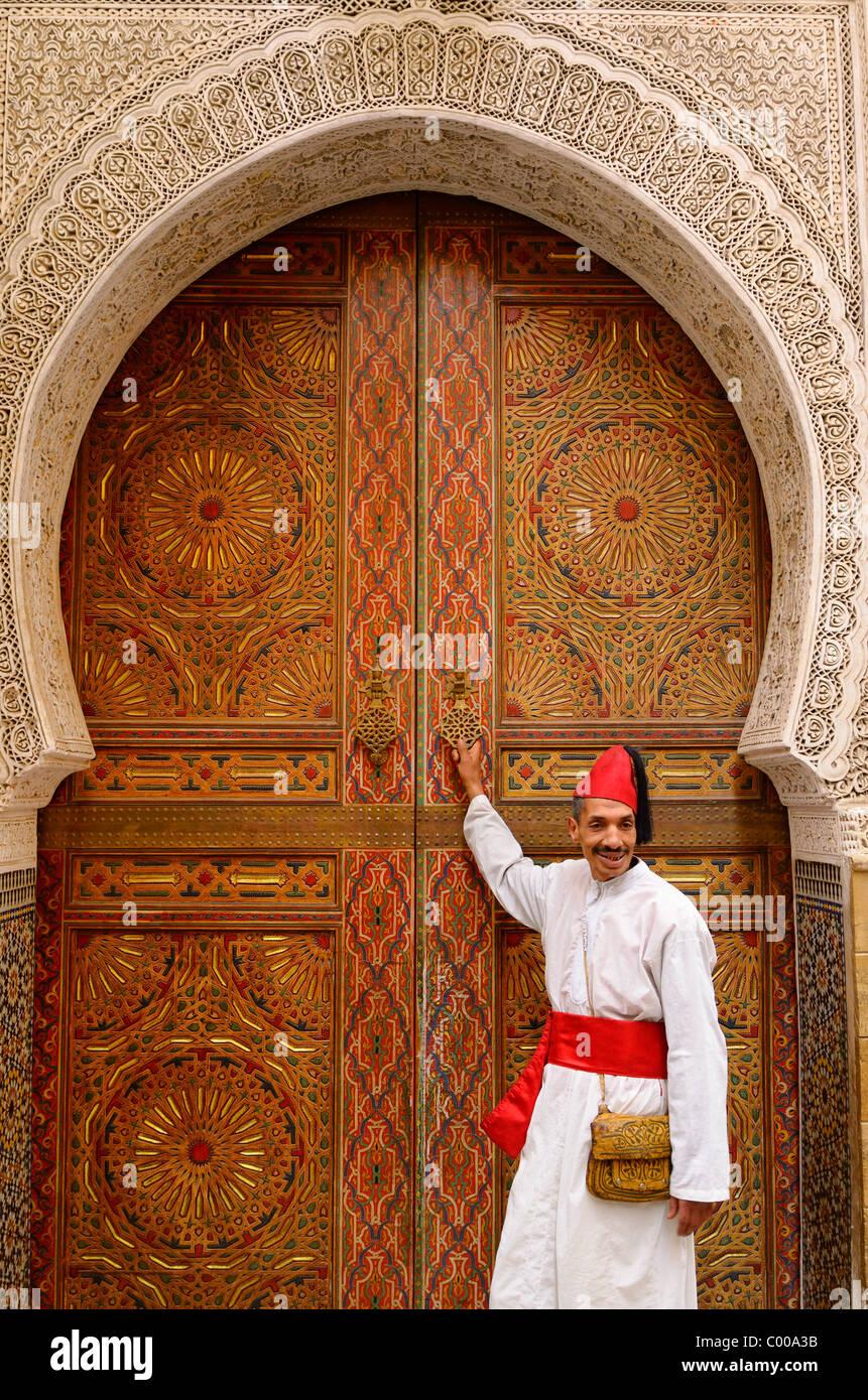 Hombre de túnica blanca y gorra roja y la guillotina en la puerta de la mezquita con intrincadas tallas de piedra y pintura en Fes el Bali Medina de Fez Marruecos, Norte de África Foto de stock