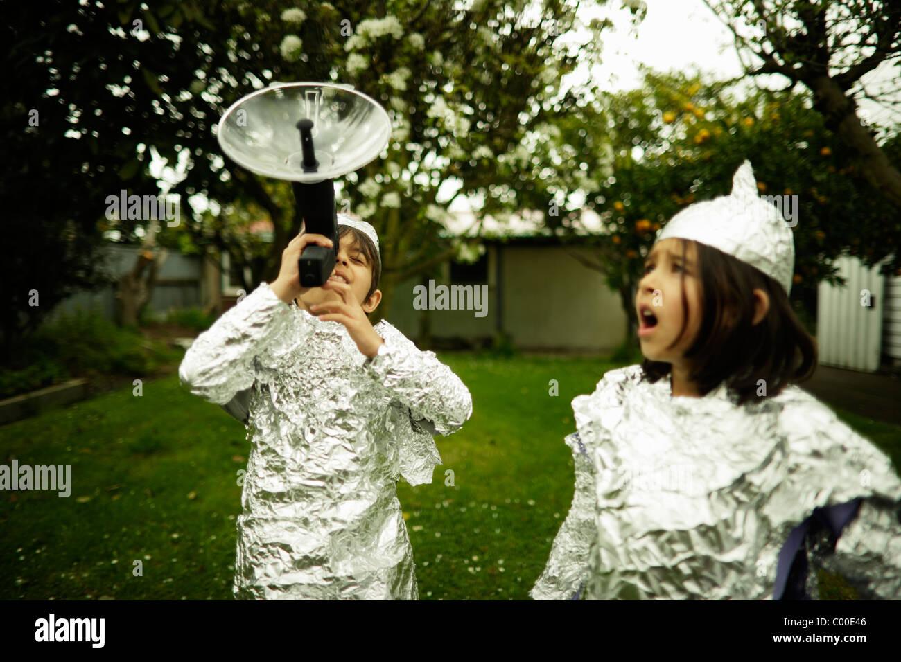 Los niños usan bicarbonato de lámina protectora mientras se ve ante una posible invasión extraterrestre. Imagen De Stock