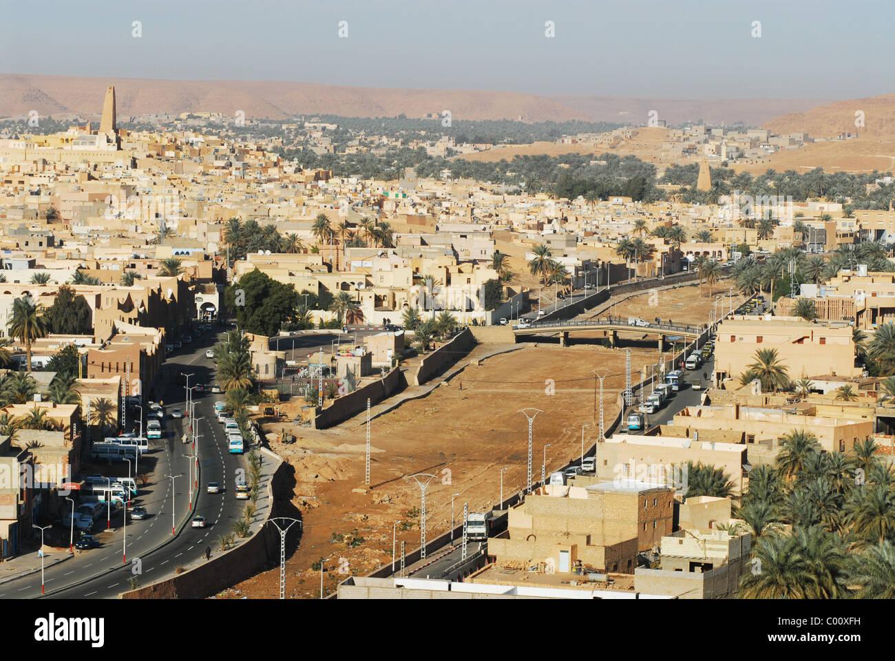 Ghardaia, Argelia, vista de la ciudad con los vehículos en carretera, vivienda de ladrillos de barro y alto minarete contra el cielo claro Foto de stock
