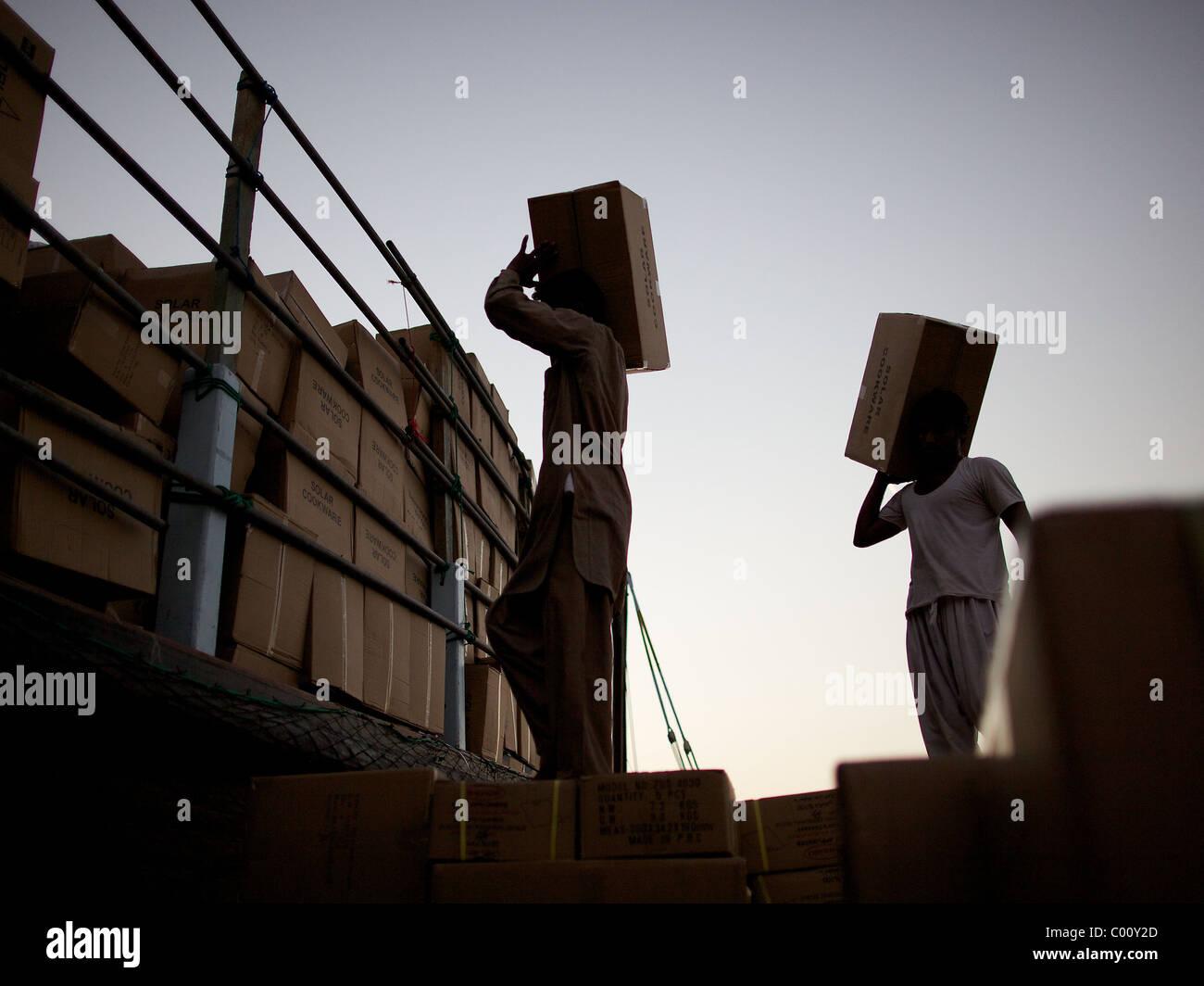 Los trabajadores cargando los tradicionales dhows después del atardecer en el dhow muelle en el Arroyo, Dubai, Imagen De Stock