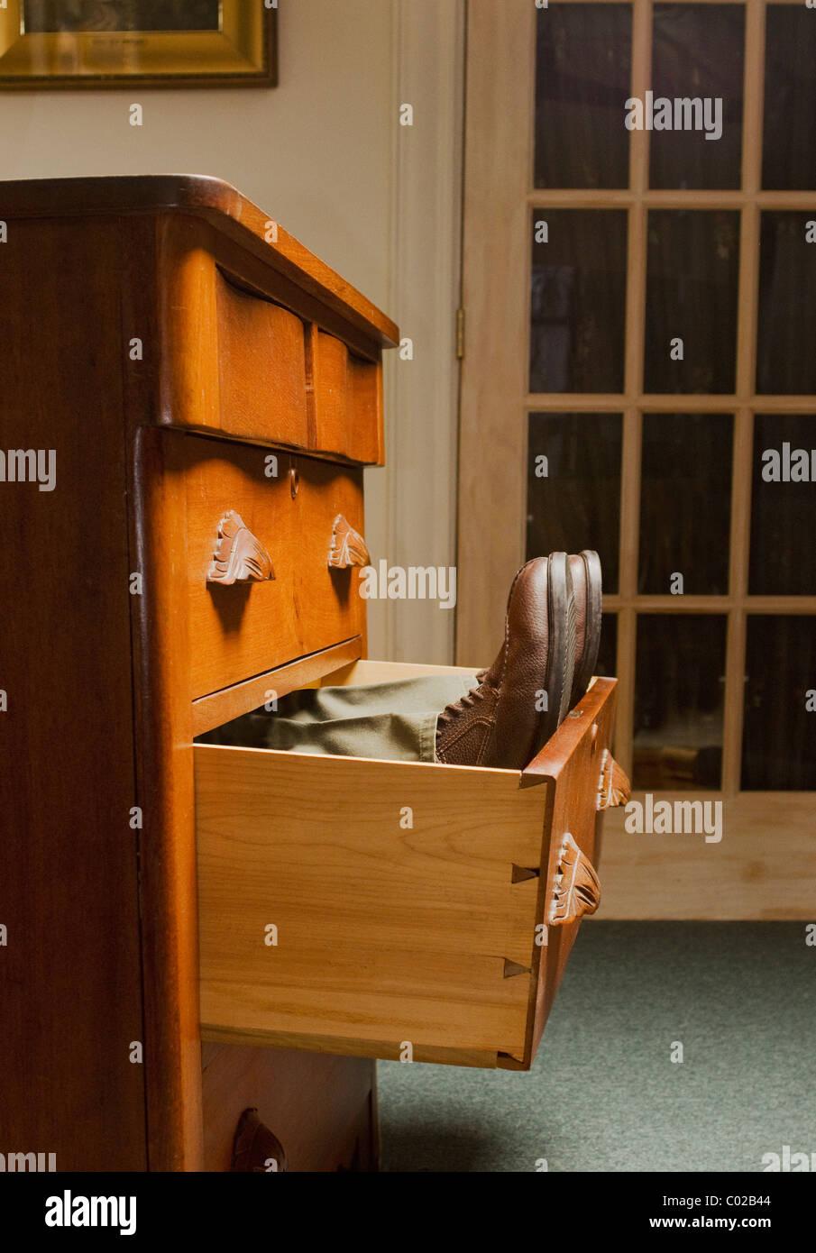 Las piernas del hombre y zapatos acostado en abrir gaveta de ropa Foto de stock