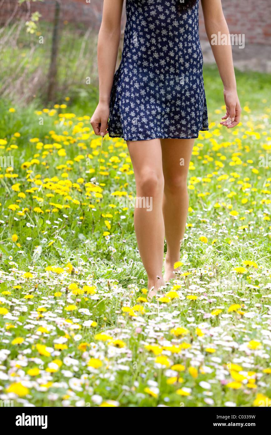 Chica caminando en un prado florido Imagen De Stock