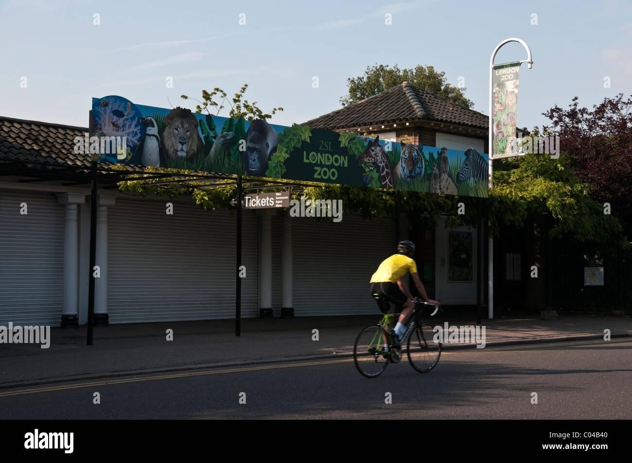 El Zoológico de Londres firmar, Jardines Zoológicos entrada y ciclista en camiseta amarilla, Regents Park, Imagen De Stock