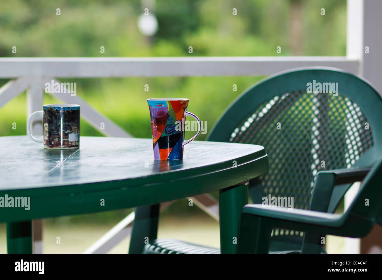 Dos tazas al aire libre en el patio con muebles de color verde ...