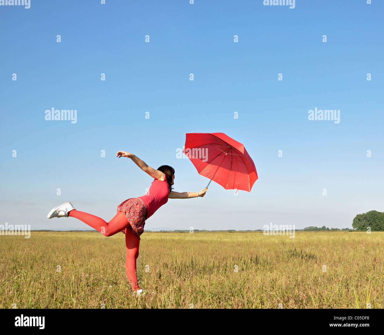 Mujer joven sosteniendo la sombrilla roja Imagen De Stock