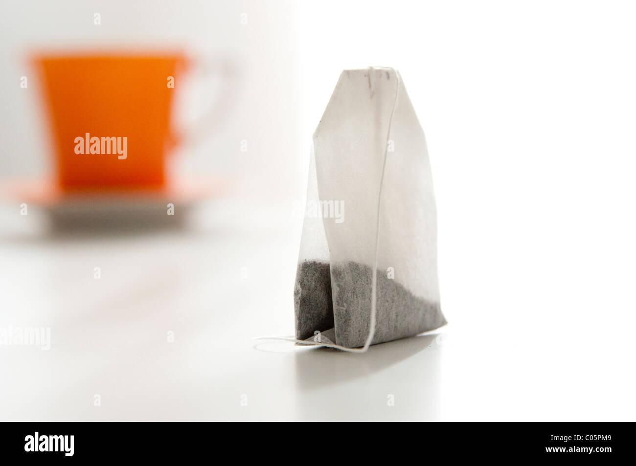 Cierre de la bolsa de té con fuera de foco taza de té de naranja en segundo plano. Imagen De Stock
