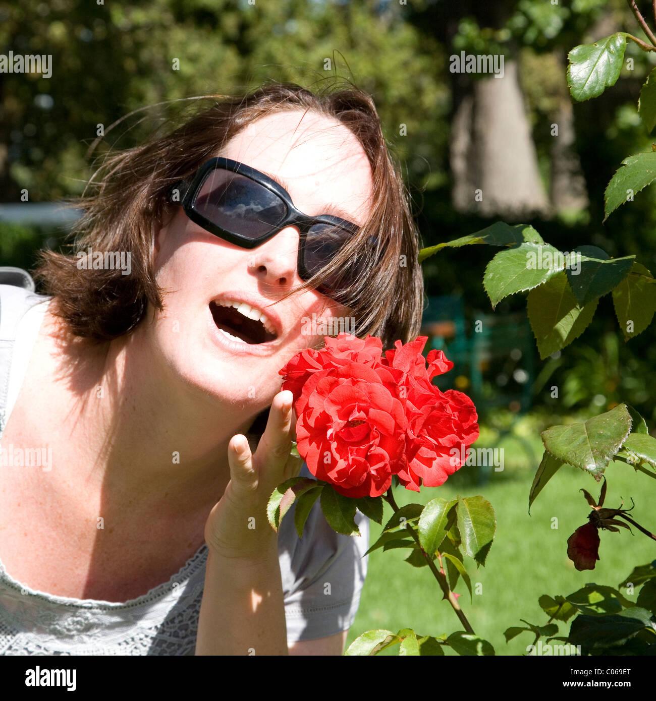 Mujer oliendo una rosa roja en el jardín Imagen De Stock