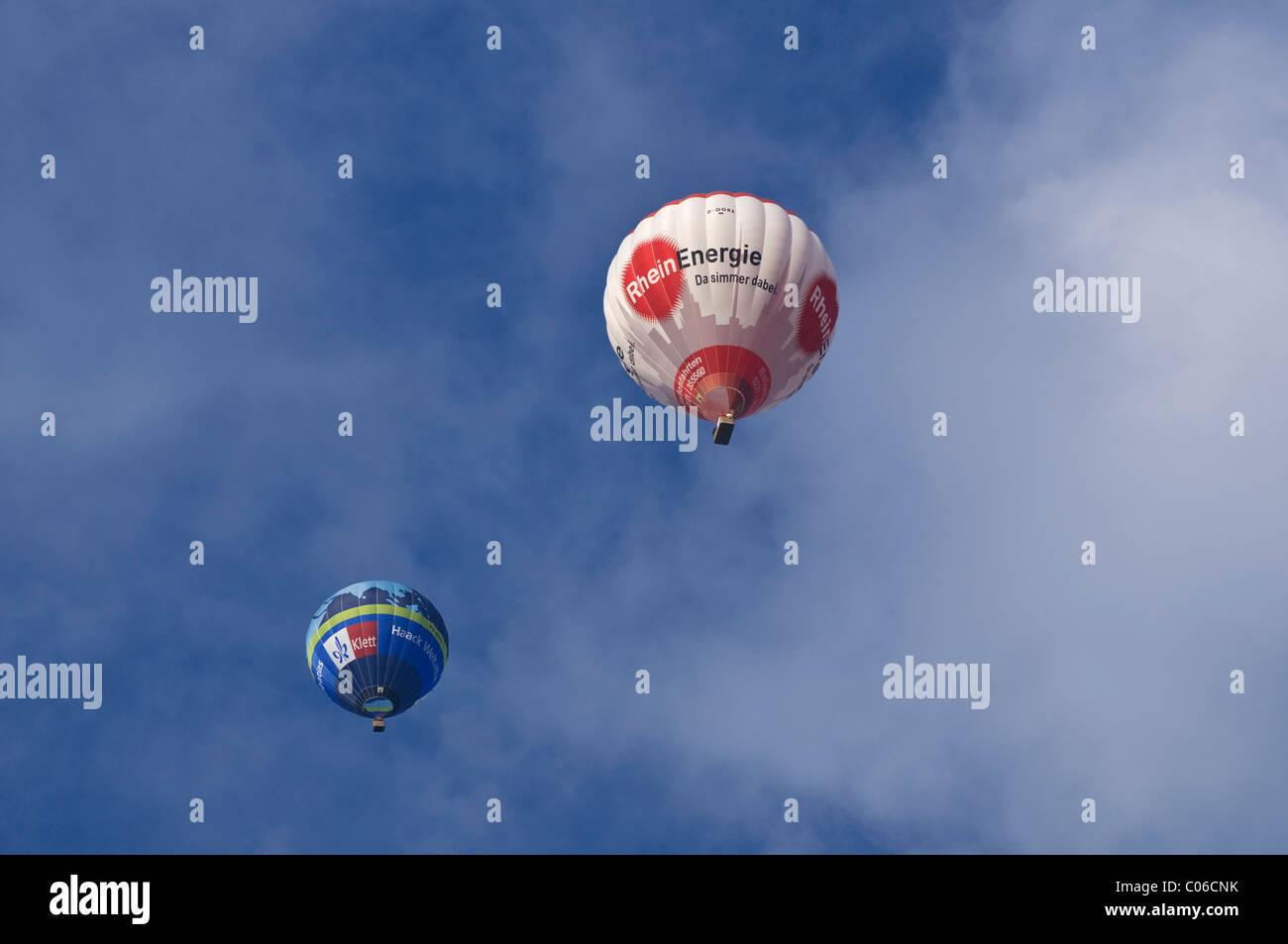 Dos globos de aire caliente, Klett Verlag y Rheinenergie, delante de un cielo nublado Imagen De Stock