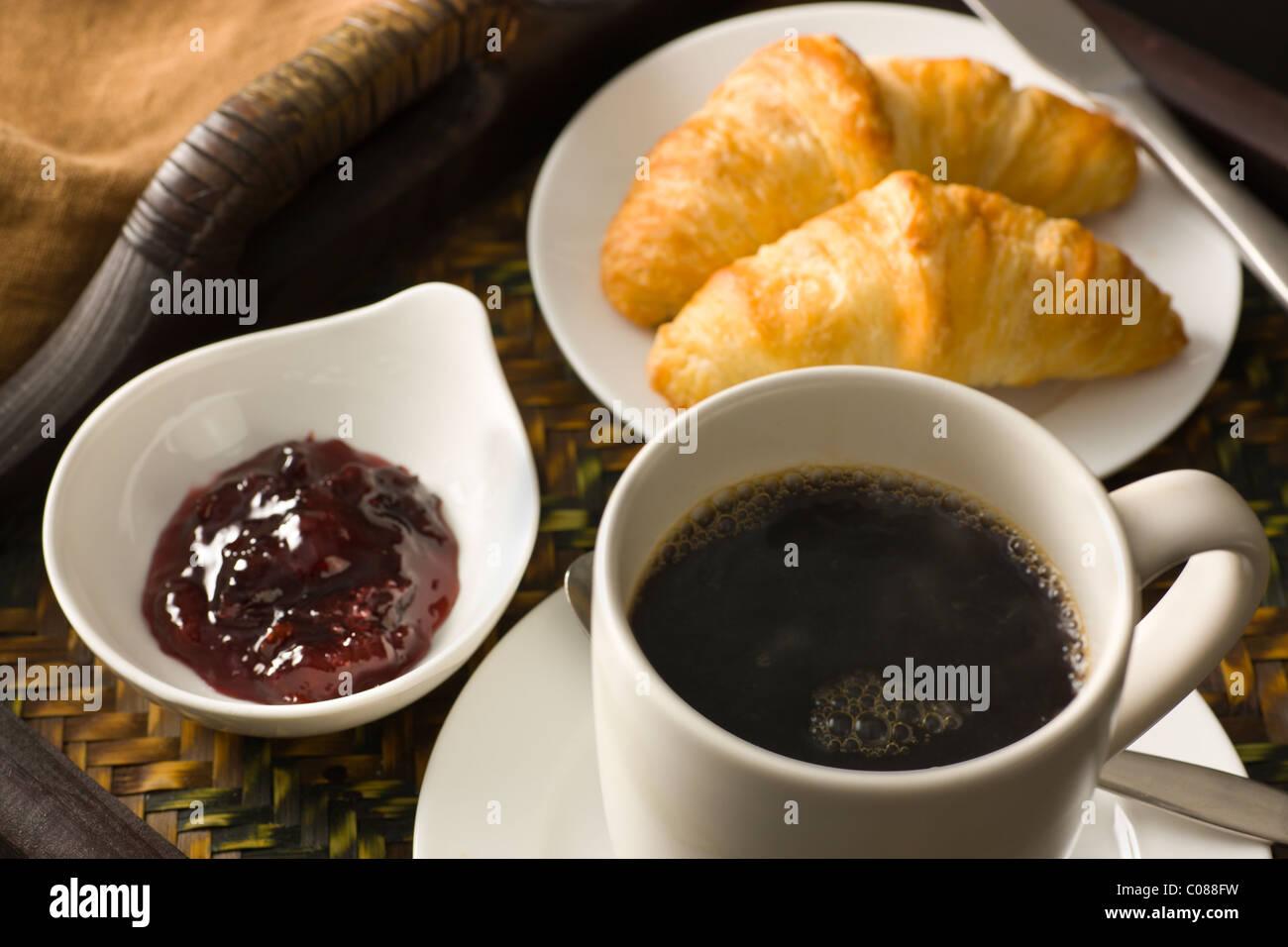 Una bandeja con cruasanes, mermelada y una taza de café negro caliente Foto de stock