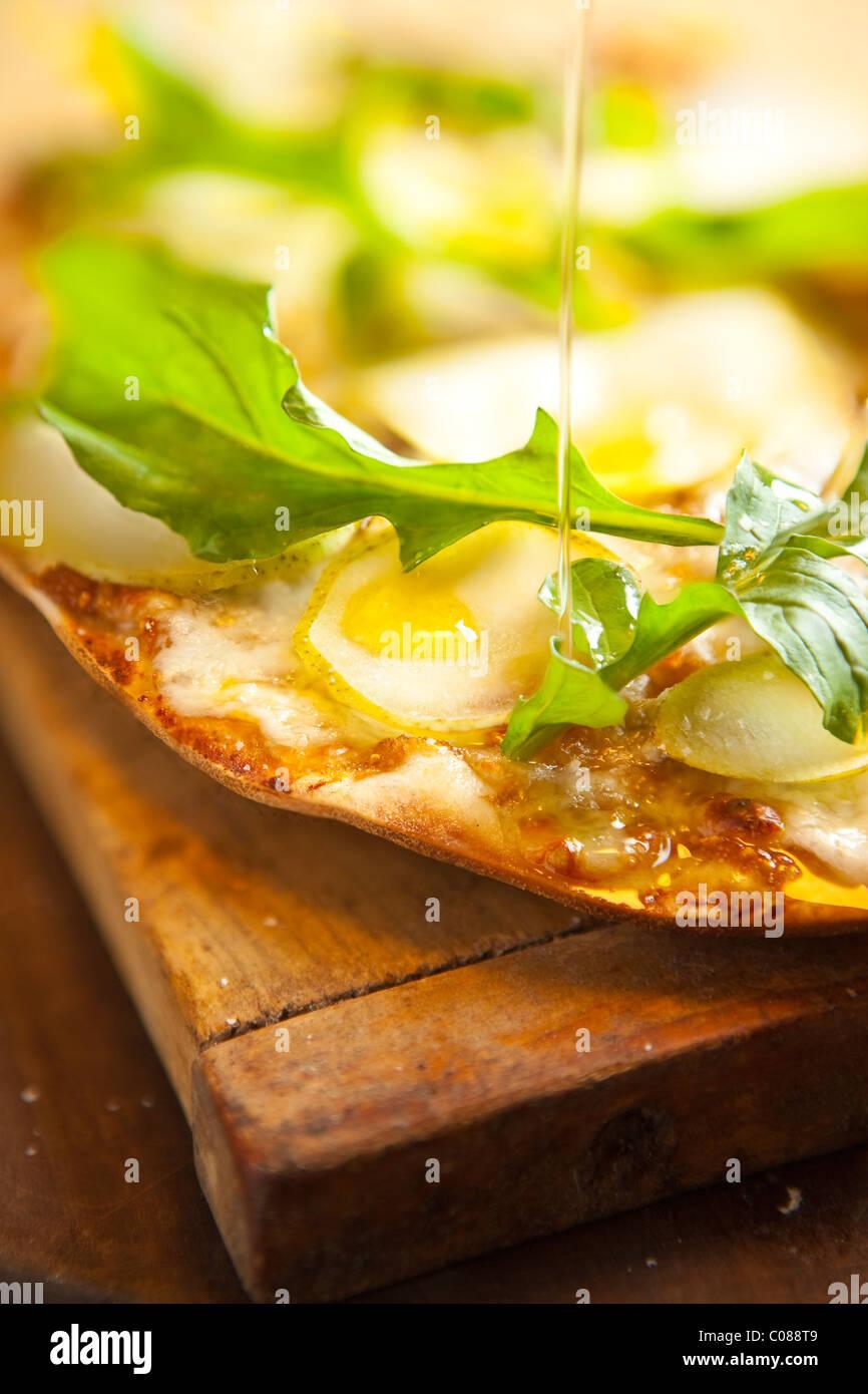 Delgado y corteza crujiente Pizza con mozzarella, queso de cabra, Fig propagación, pera y rúcula preparado Imagen De Stock