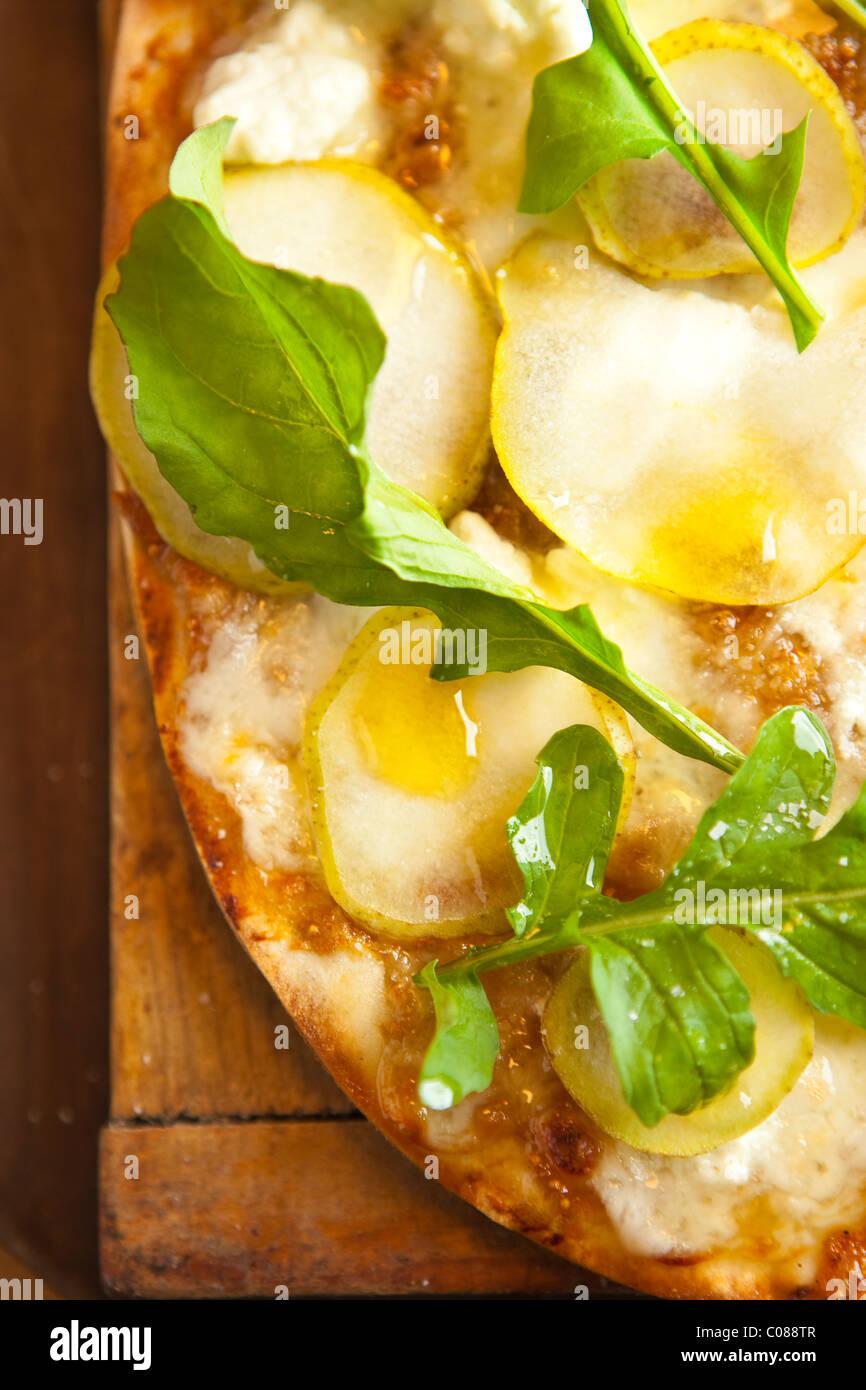 Delgado y corteza crujiente Pizza con mozzarella, queso de cabra, Fig propagación, pera y rúcula preparado por Gianni Foto de stock