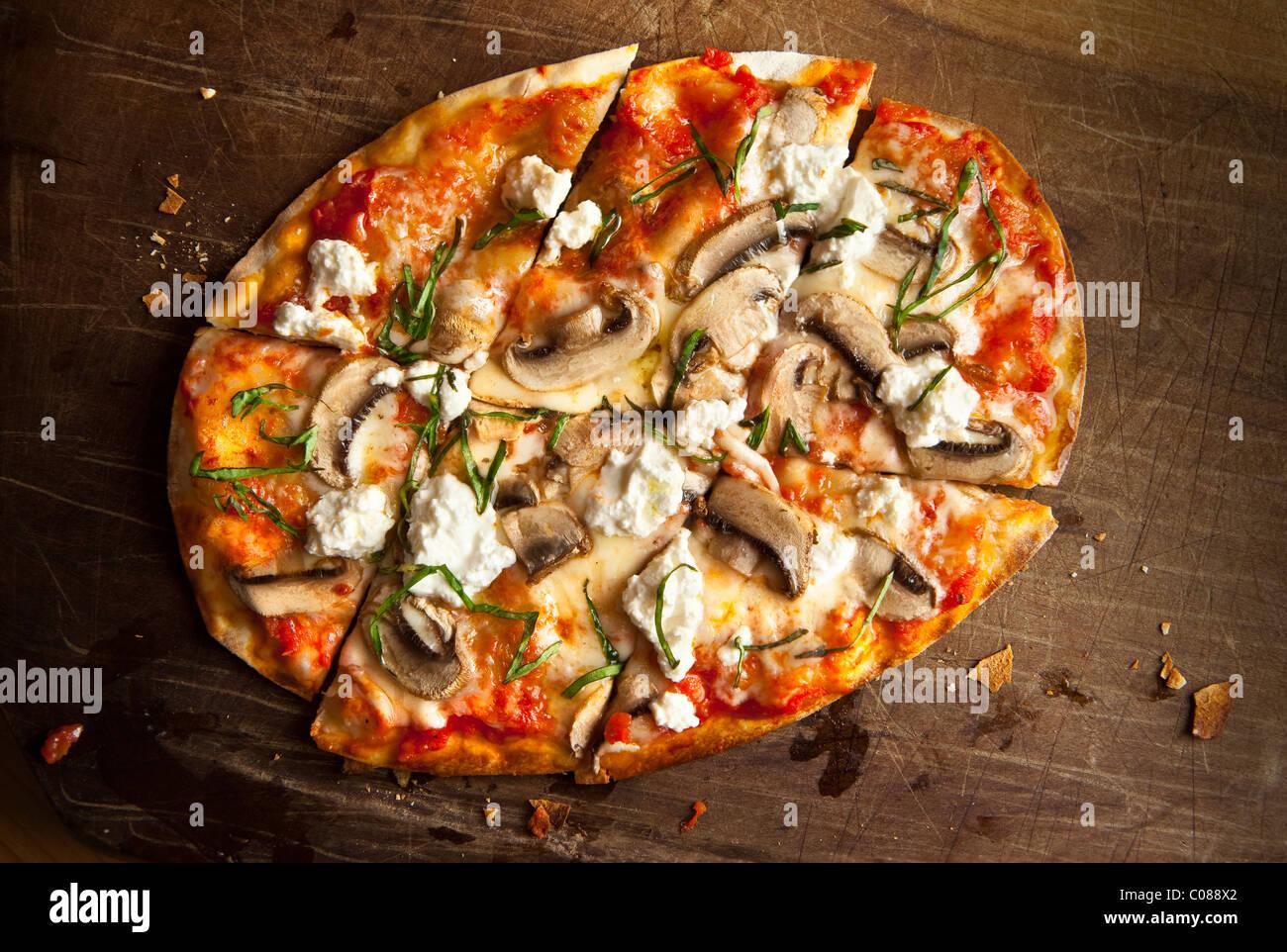 Delgado y corteza crujiente Pizza con mozzarella, champiñones, queso de cabra y Albahaca preparado por Gianni Imagen De Stock
