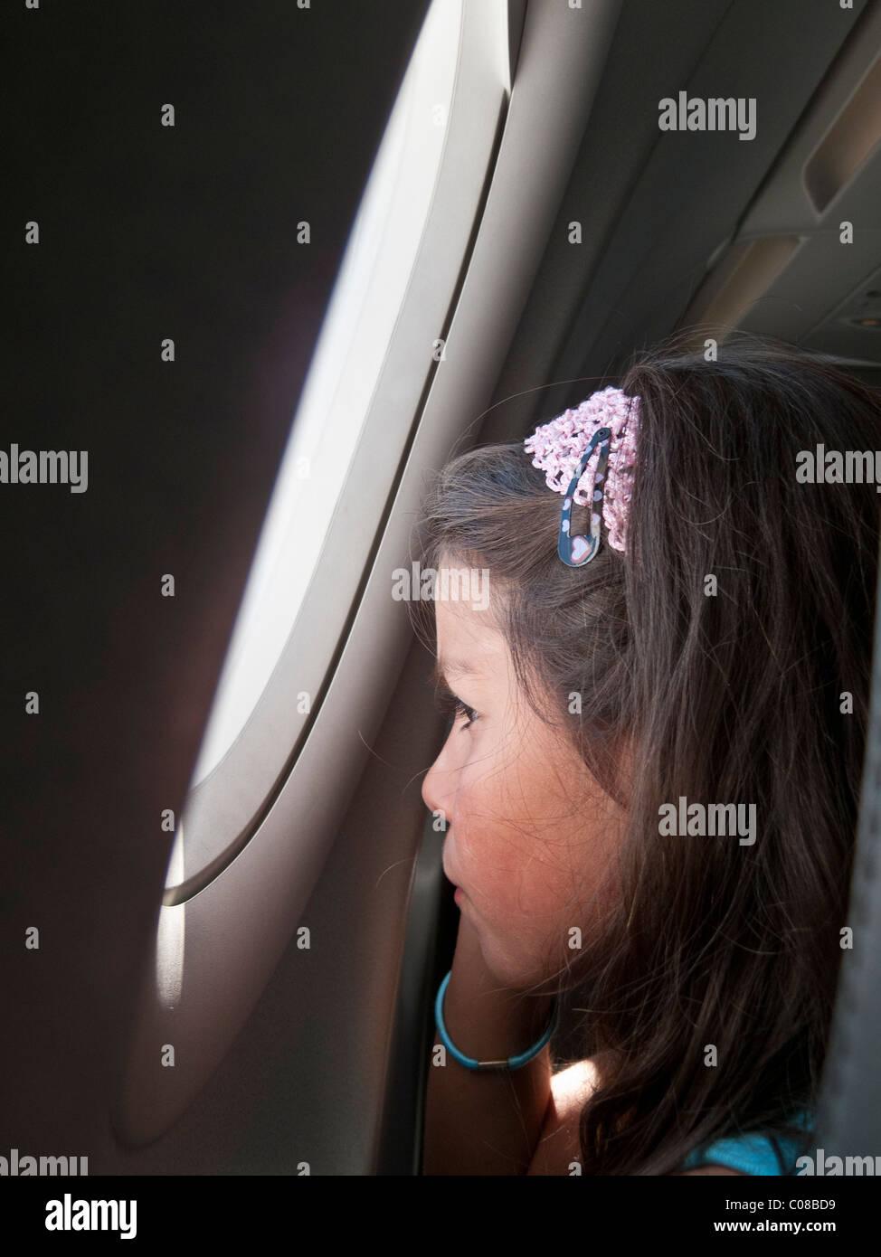 Niño en un avión, mirando por la ventana Foto de stock