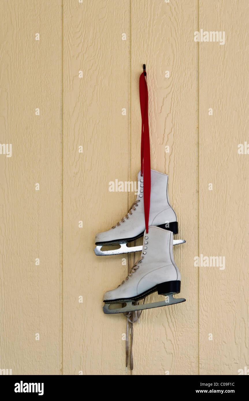 Patines de hielo que cuelgan de una cinta roja como decoración de vacaciones en Floyds, perillas, Indiana Imagen De Stock