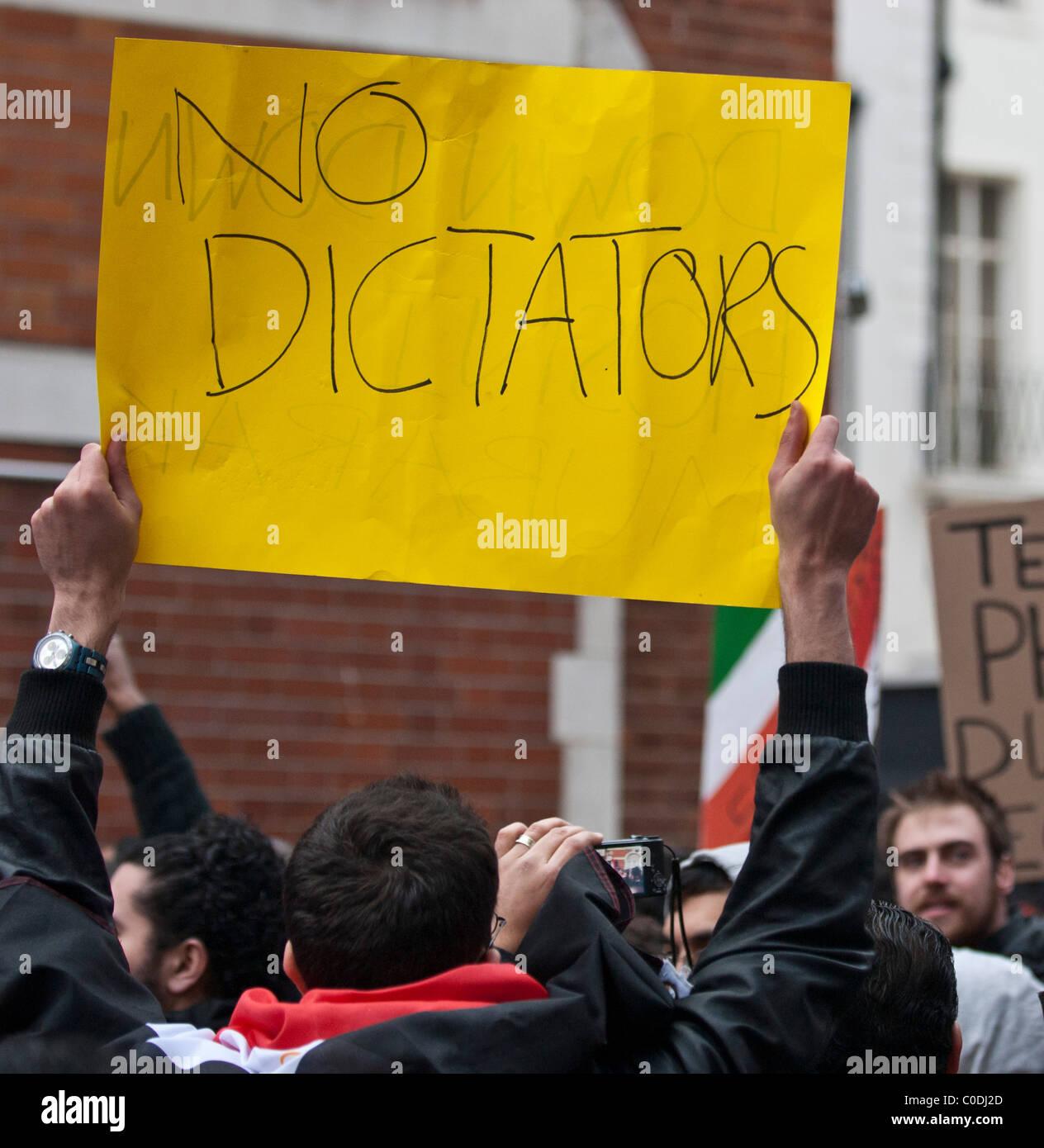 "Manifestante contra Hosni Mubarak sostiene pancarta diciendo 'no dictadores"" fuera de la Embajada egipcia Imagen De Stock"