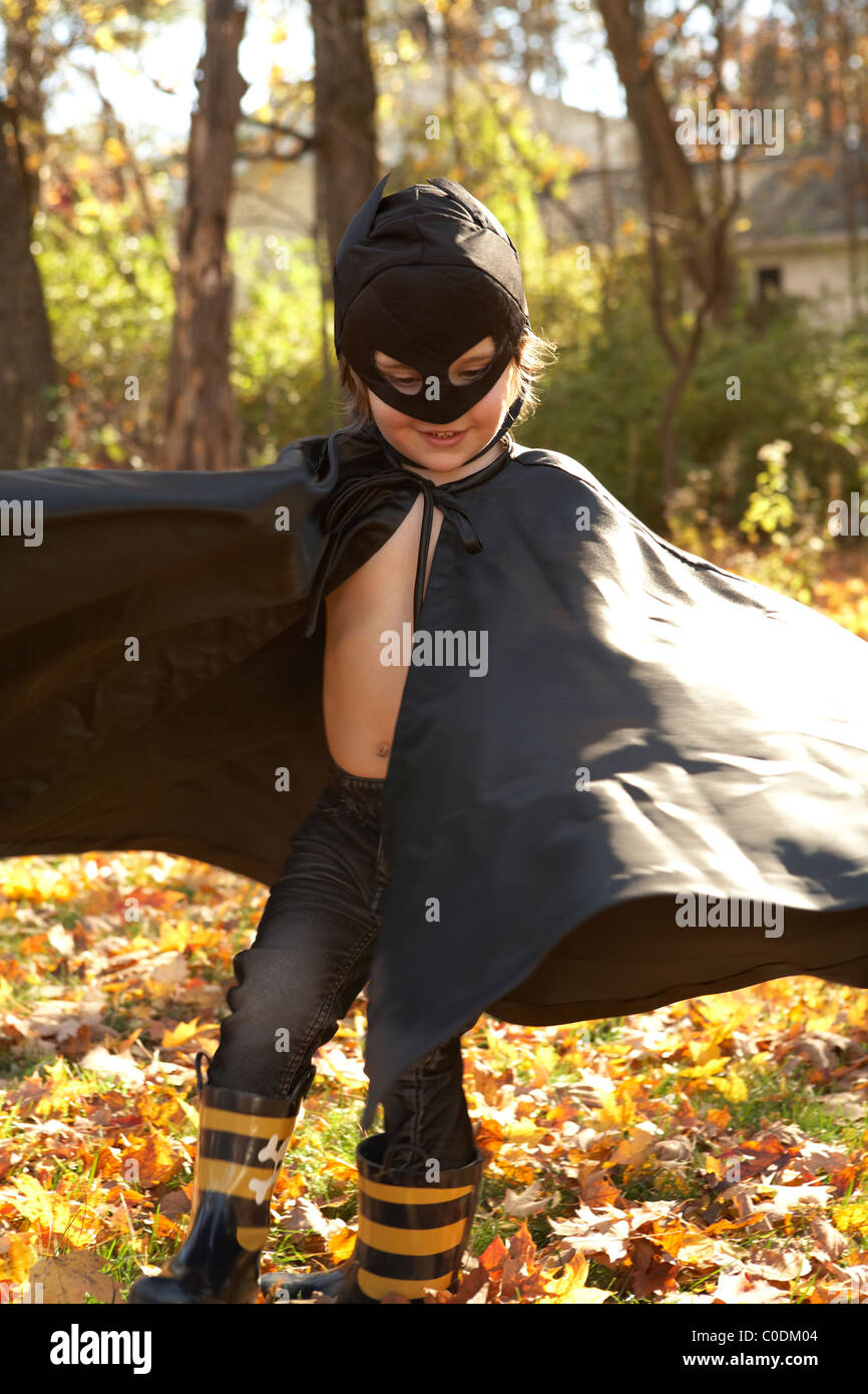Kid vestido como Batman jugando en las hojas Foto de stock