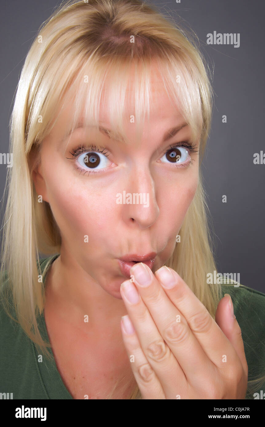 Conmocionada mujer rubia con la mano delante de la boca contra un fondo gris Imagen De Stock
