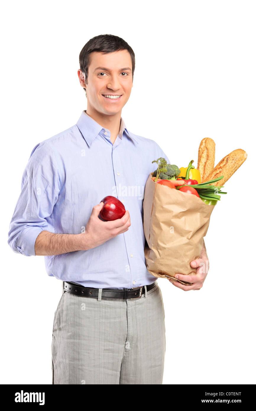Hombre sonriente sosteniendo una manzana, una bolsa llena de