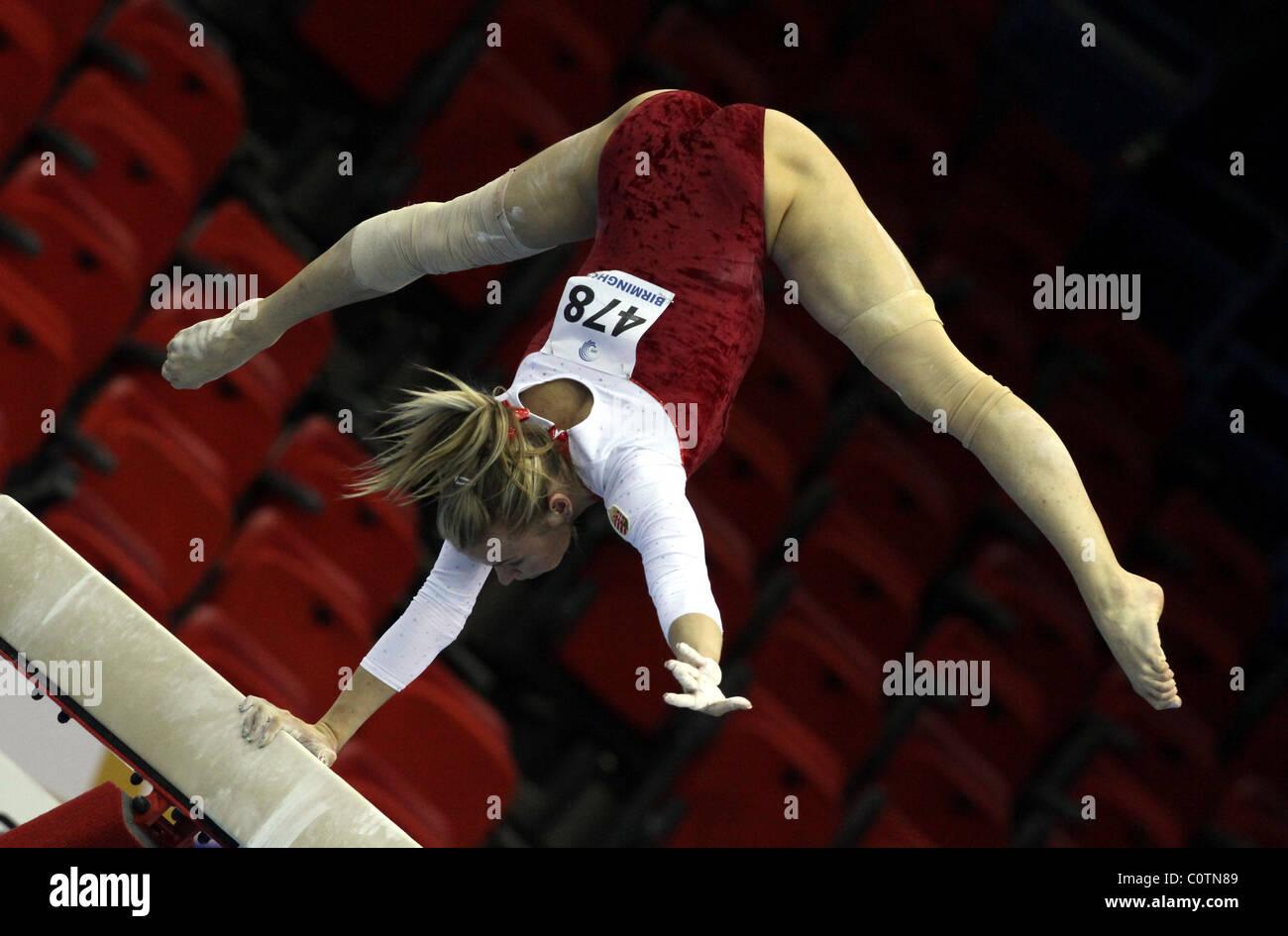 Gimnasta femenino realiza un pino usando sólo un brazo en la viga, en una competencia de gimnasia Imagen De Stock