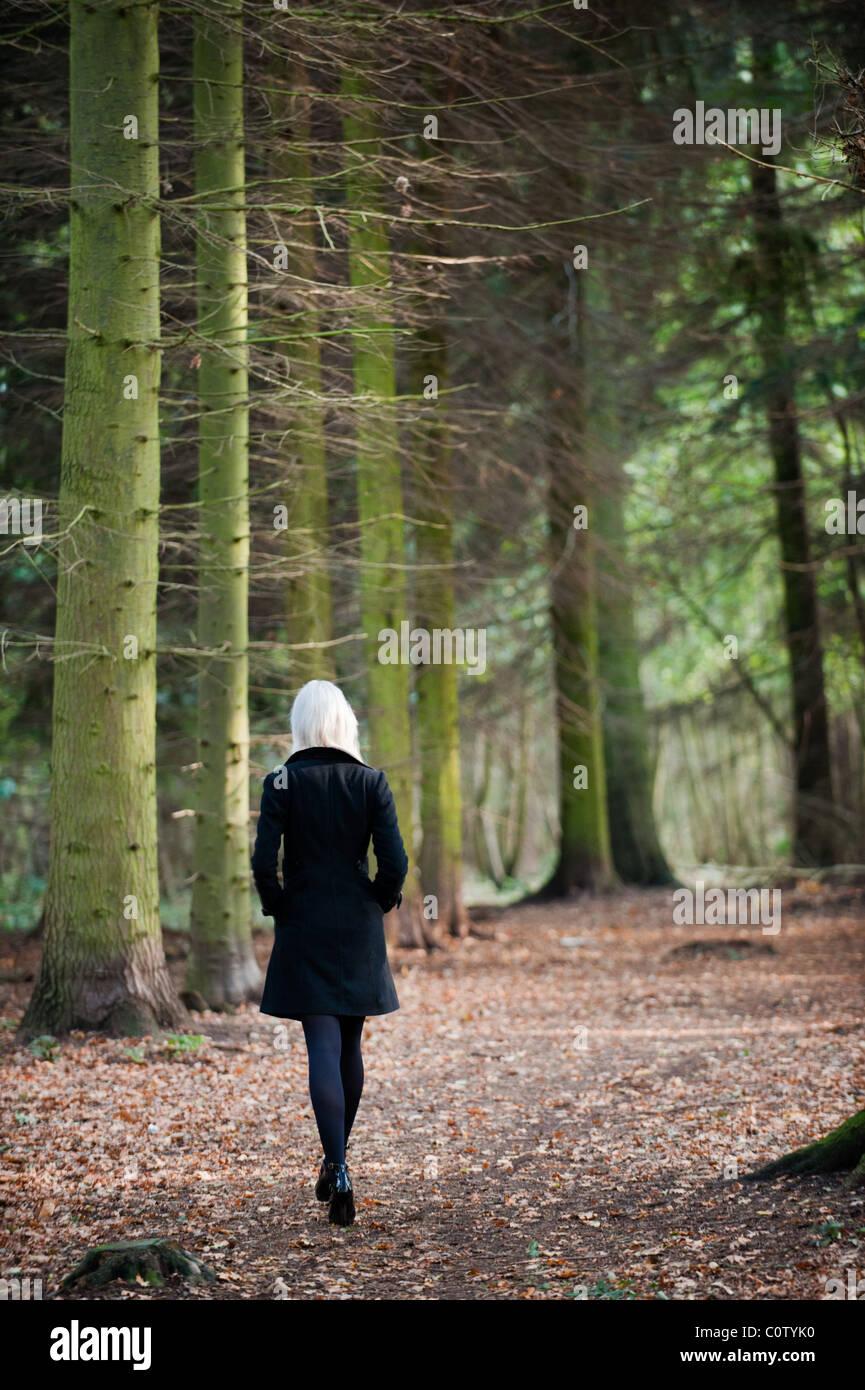 Joven Rubia modelo en negro stiletto zapatos y abrigo caminar solo a través de los bosques en otoño caen Foto de stock