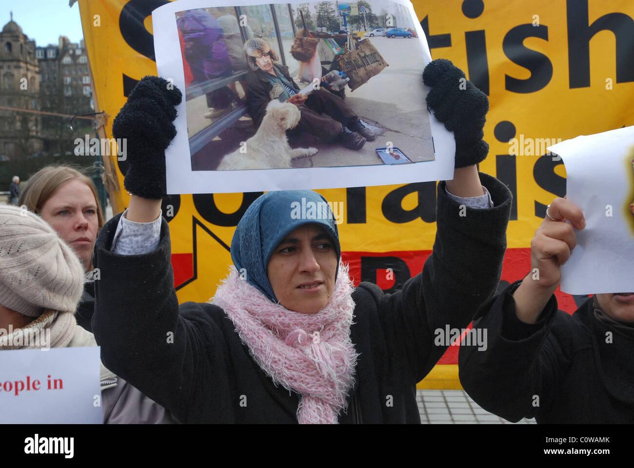Un manifestante sostiene una foto burlarse Col.Gadaffi a una manifestación en el montículo en Edimburgo, Imagen De Stock
