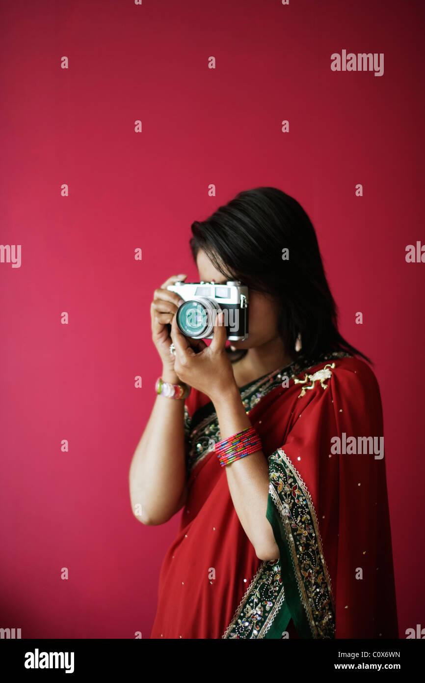 Punjabi mujer en rojo sari toma una imagen con la cámara de película antigua Imagen De Stock