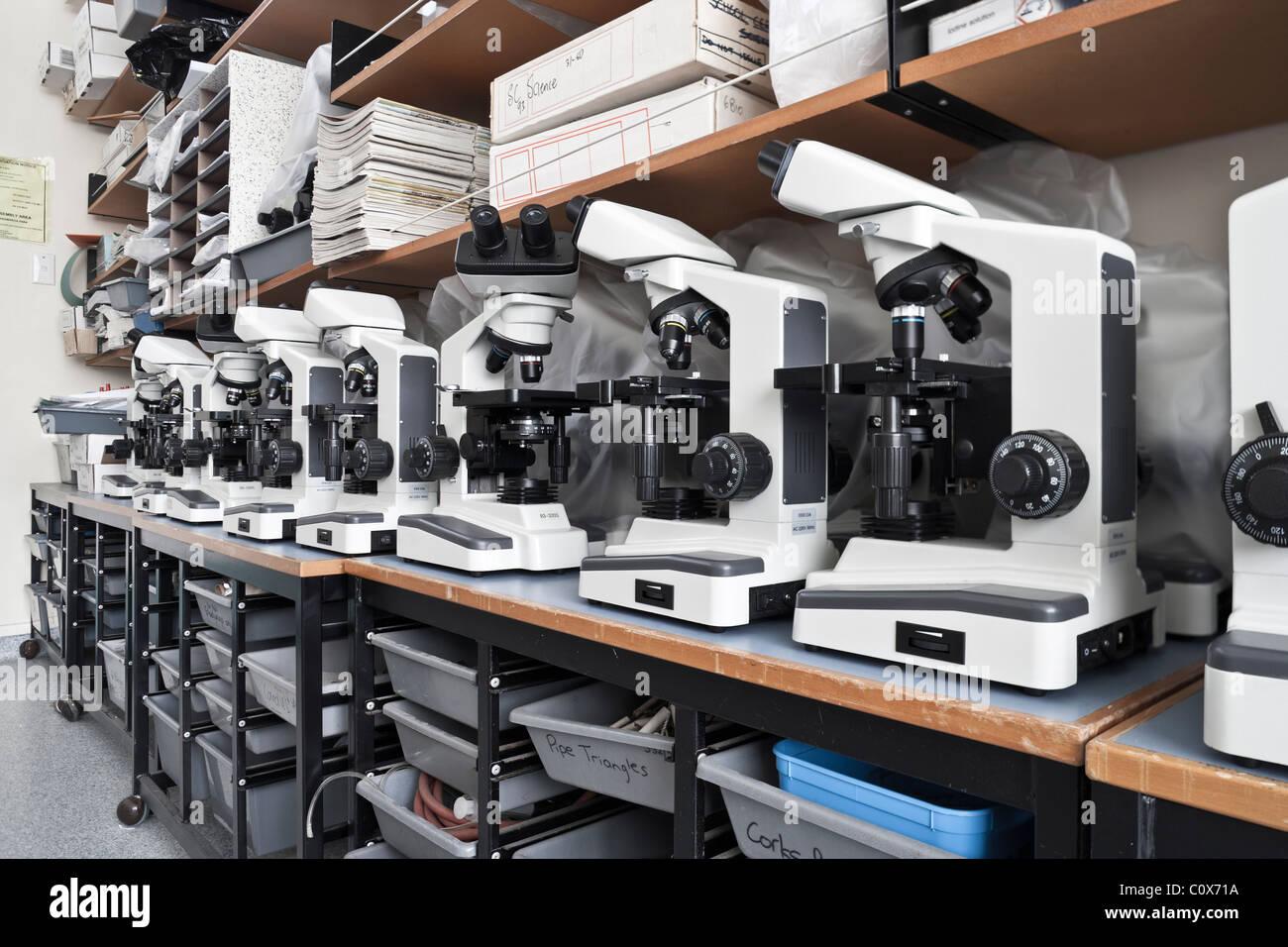Fila de microscopios en almacén de biología de la escuela. Logotipos extraídos. Imagen De Stock