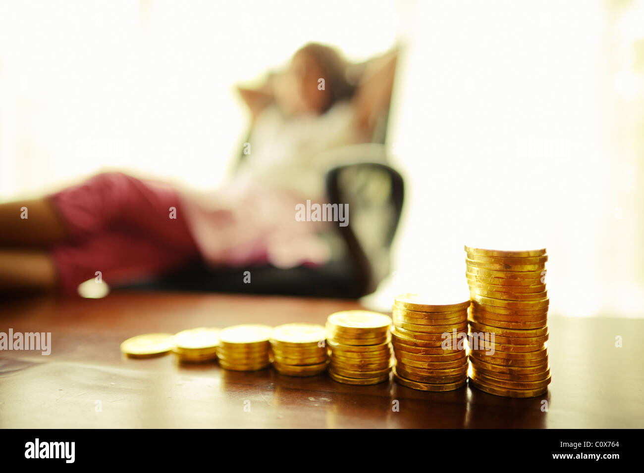 Invertir en oro. Chica con monedas de oro de chocolate apiladas. Imagen De Stock