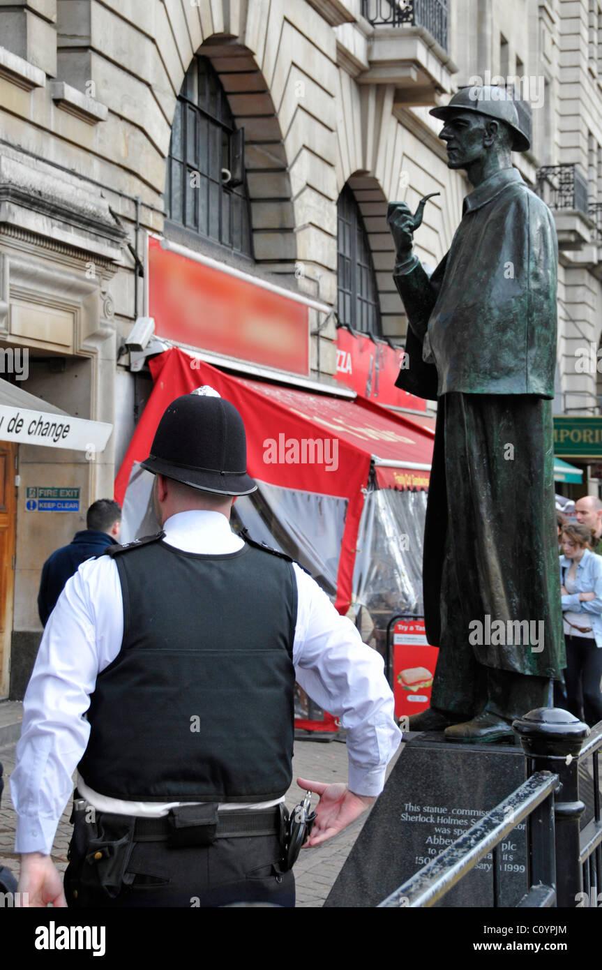 Beat policía patrullando zonas turísticas fuera de la estación de Baker Street con Sherlock Holmes escultura más allá de oscurecida firmar Foto de stock
