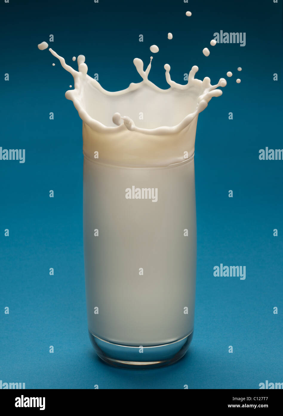 Splash de leche desde el cristal sobre un fondo azul. Imagen De Stock