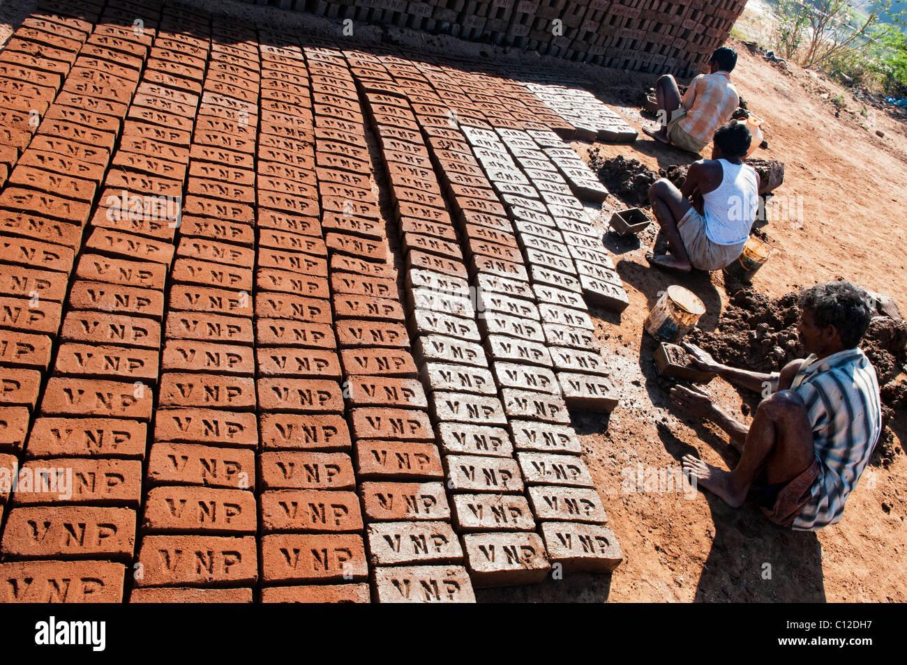 Hombres indios haciendo ladrillos de la casa con la mano utilizando un molde y arcilla húmeda / barro. El secado Imagen De Stock