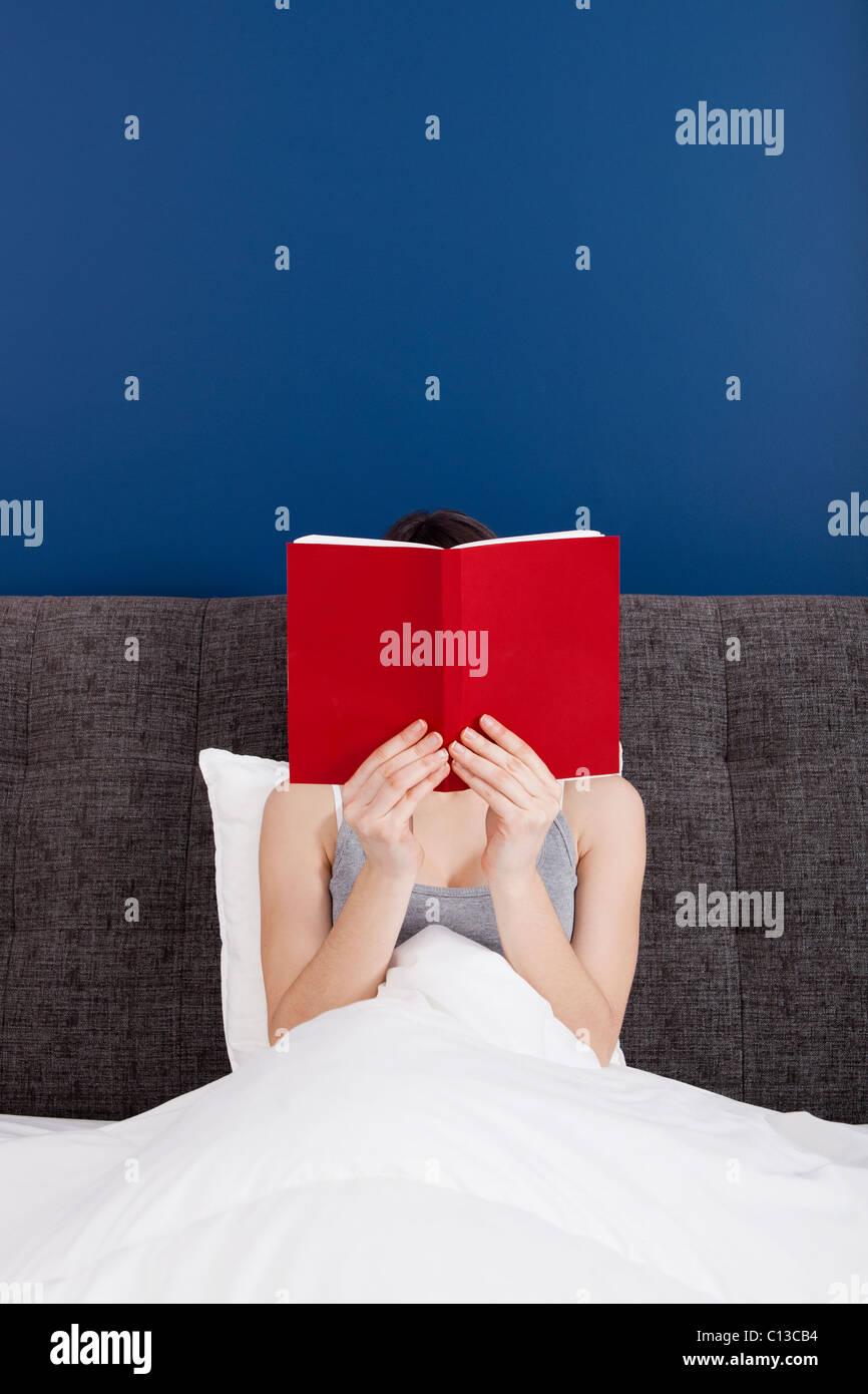 Mujer leyendo un libro con el rostro cubierto por el libro Imagen De Stock