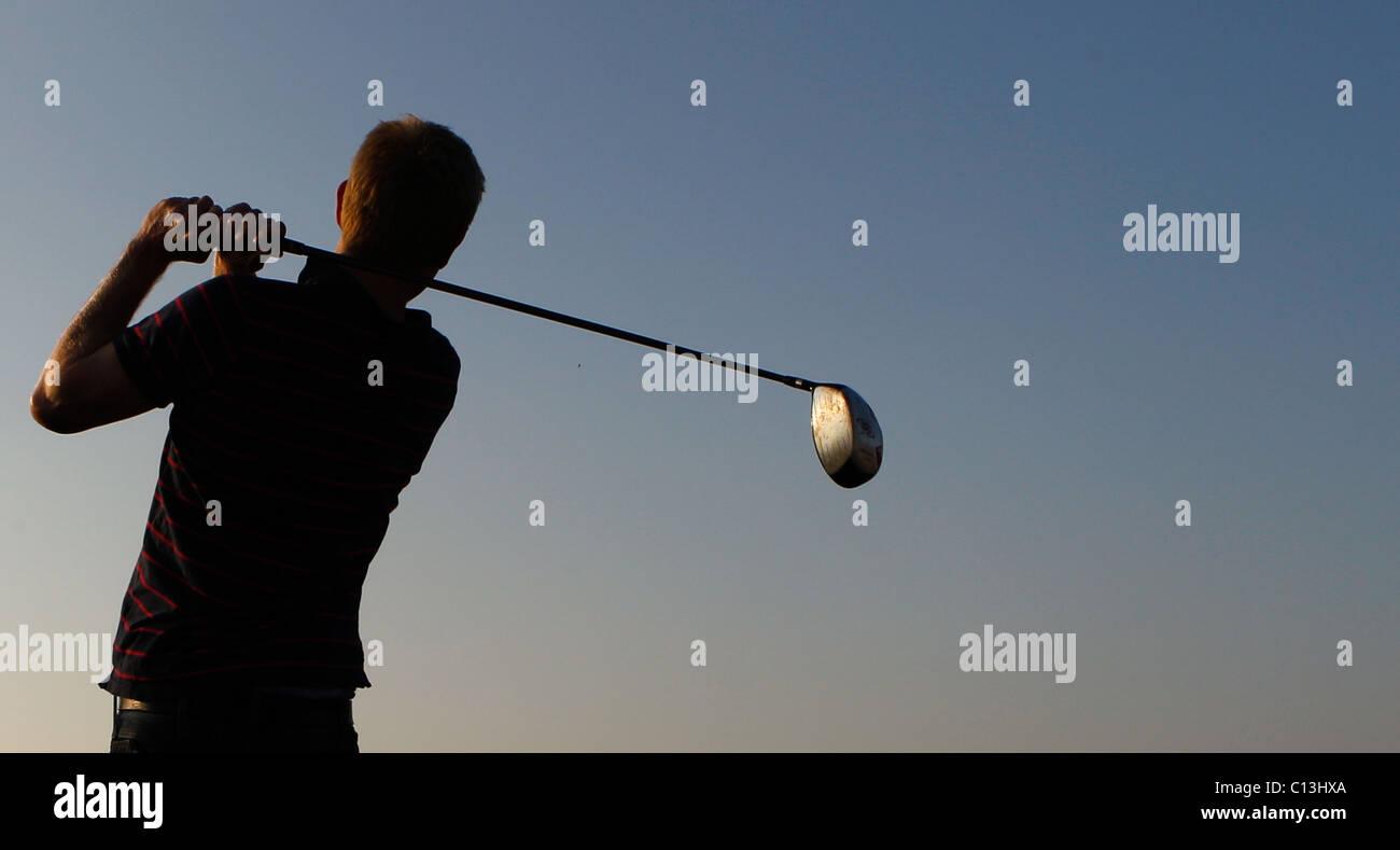 Hombre, jugar al golf con un pintoresco paisaje que le rodea mientras se pone el sol Imagen De Stock