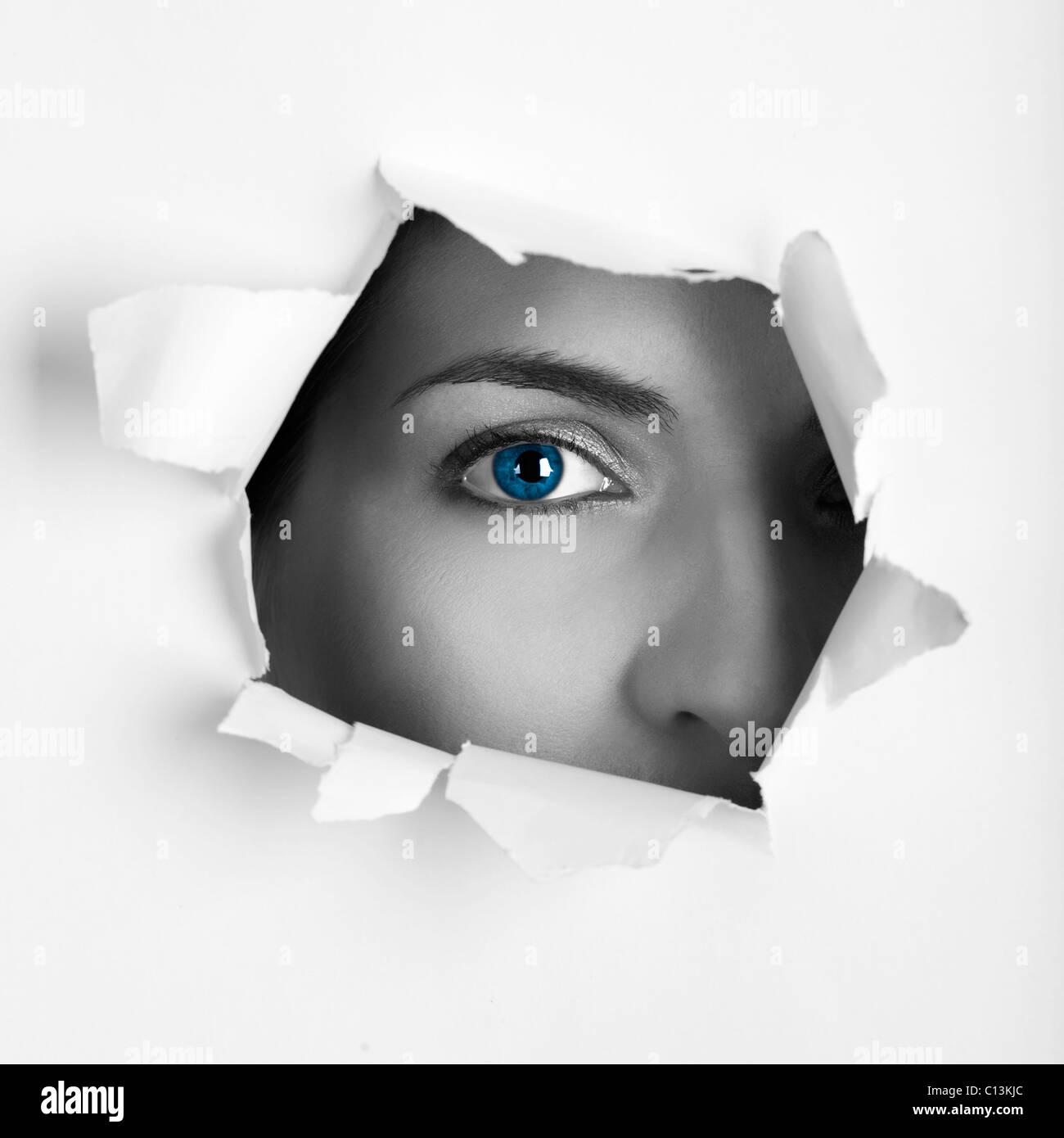 Hermosa hembra blue eye mirando a través de un orificio en una hoja de papel. Foto de stock